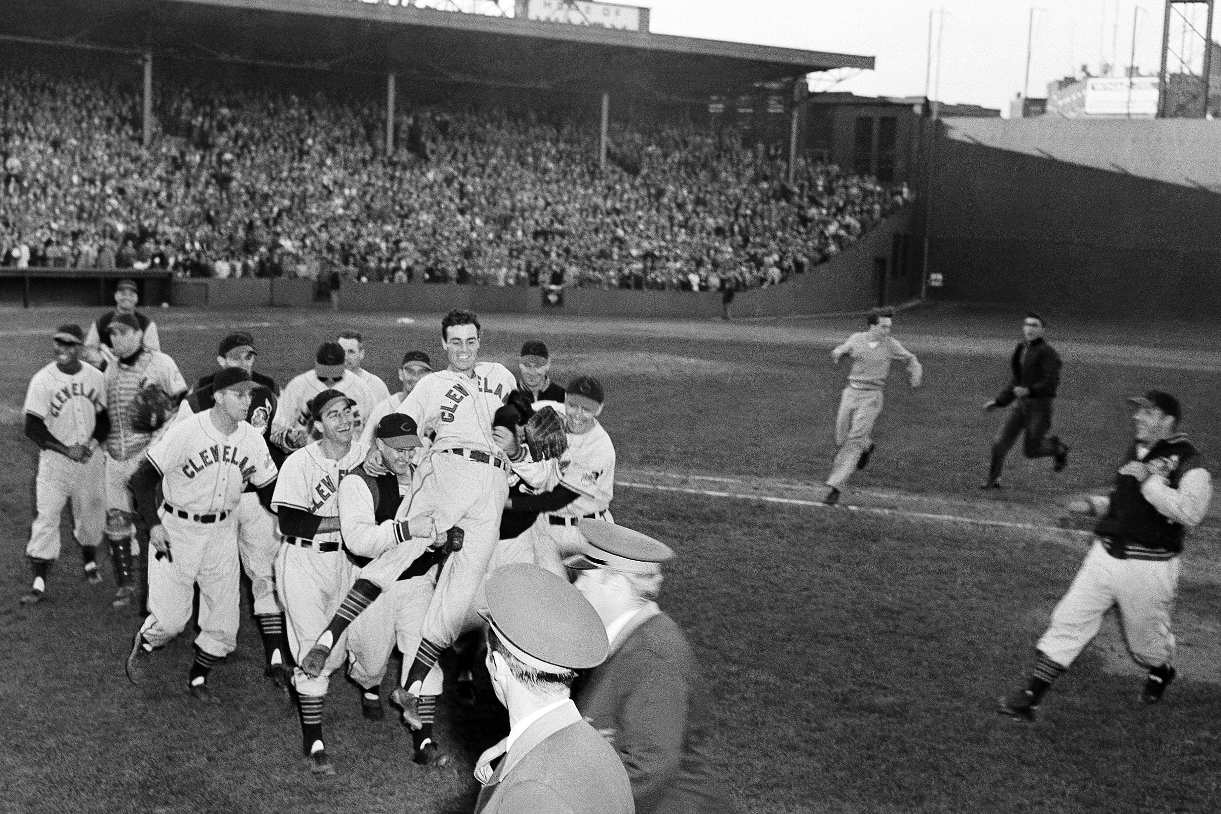 FILE - In this Oct. 4, 1948, file photo, Cleveland Indians pitcher Gene Bearden is carried off the field by teammates after their 8-3 win over the Boston Red Sox in a baseball game for the American League pennant at Fenway Park in Boston.  (AP Photo/File)