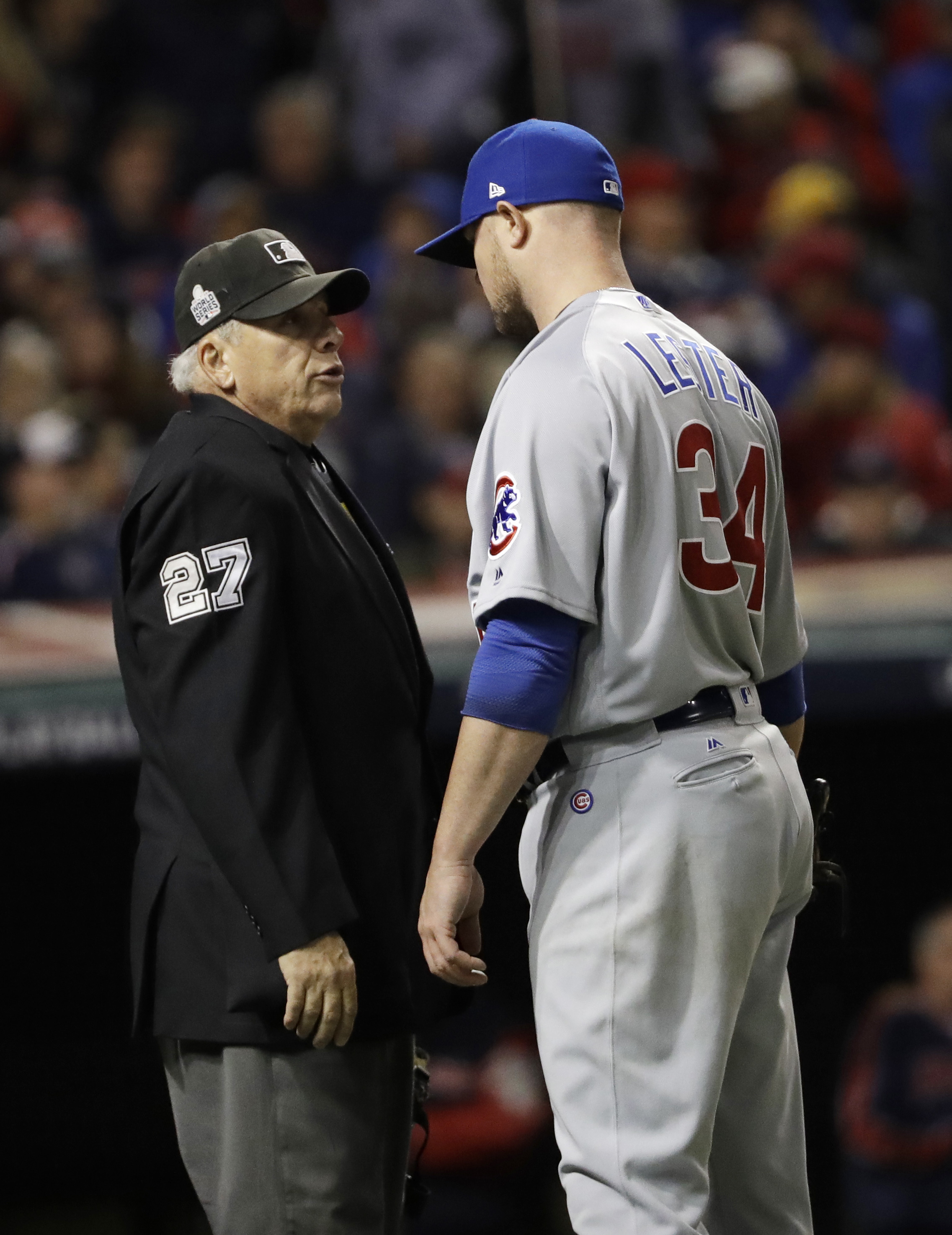 Chicago Cubs starting pitcher Jon Lester talks to home plate umpire Larry Vanover after the third inning of Game 1 of the Major League Baseball World Series against the Cleveland Indians Tuesday, Oct. 25, 2016, in Cleveland. (AP Photo/David J. Phillip)