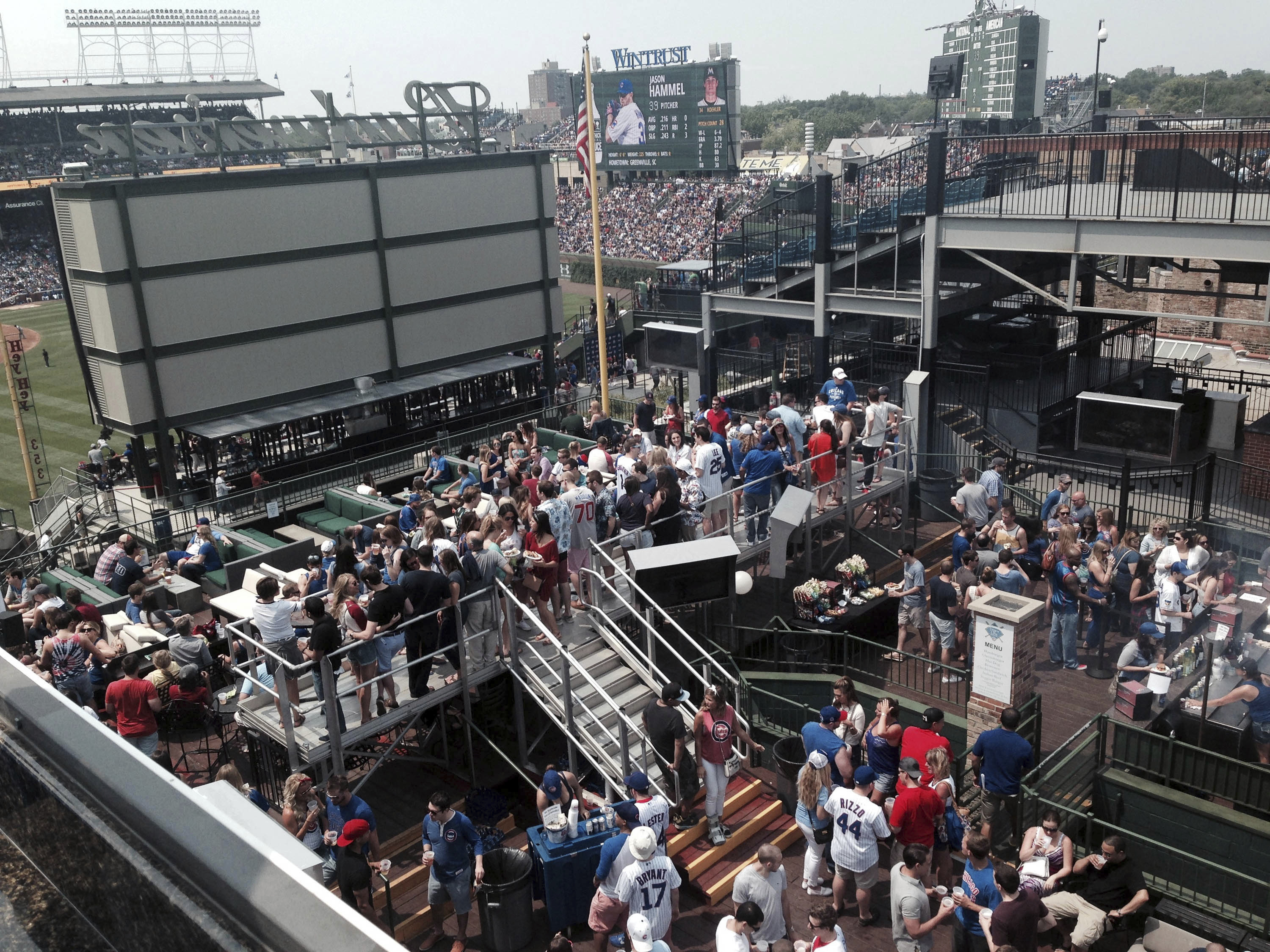 FILE - In this July 3, 2015 file photo, fans watch what they can of a baseball game between the Miami Marlins and the Chicago Cubs on a rooftop across the street from Wrigley Field in Chicago. Not since Oct. 10, 1945, has a World Series game been played a