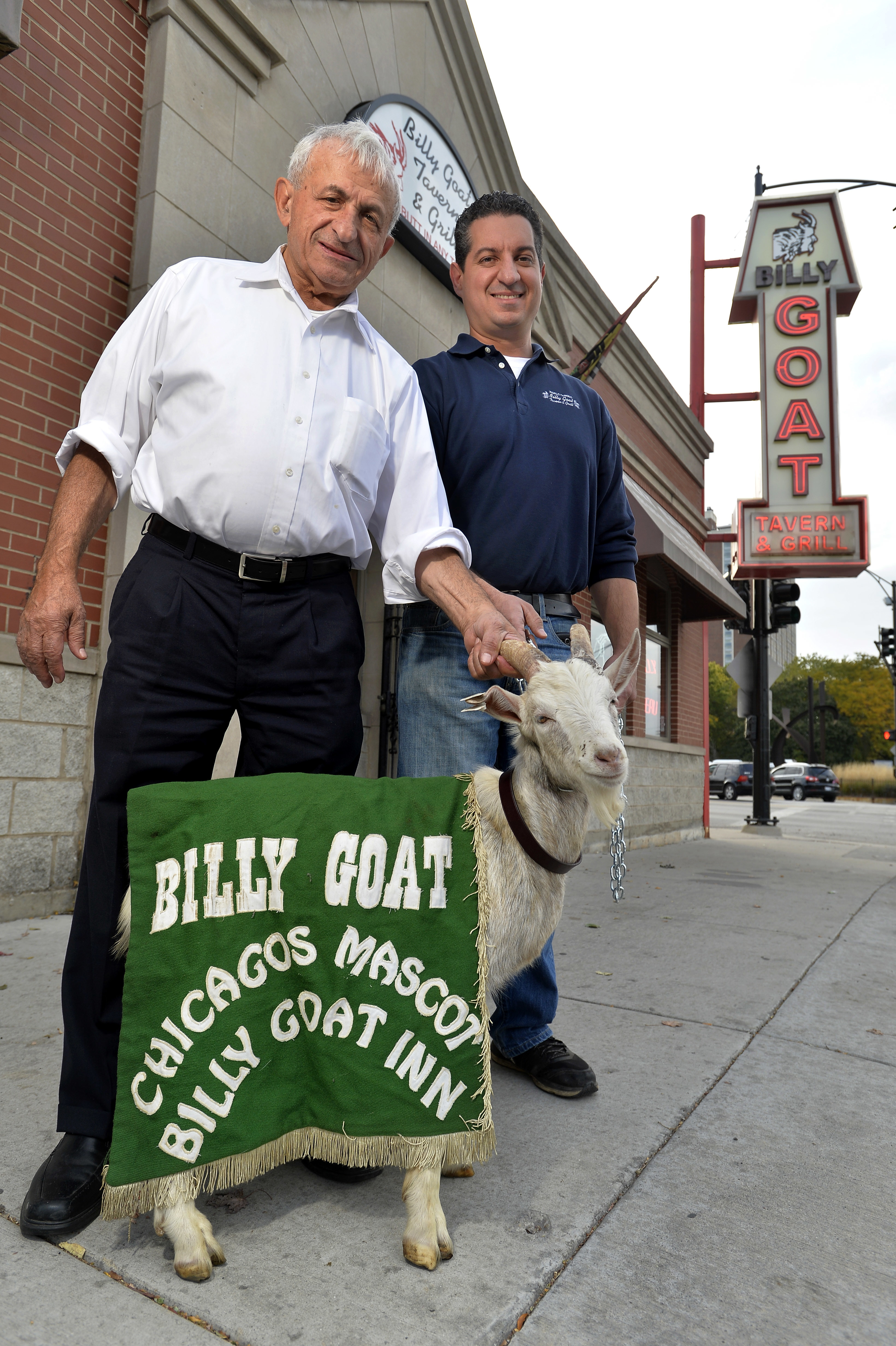 """FILE - In this Oct. 20, 2015 file photo, Billy Goat Tavern owners Sam Sianis, left, and his son Bill pose with """"Billy"""" the goat outside their tavern on Madison Street in Chicago. In 1945 Sam's uncle, William, cast a curse over the Chicago Cubs for not let"""
