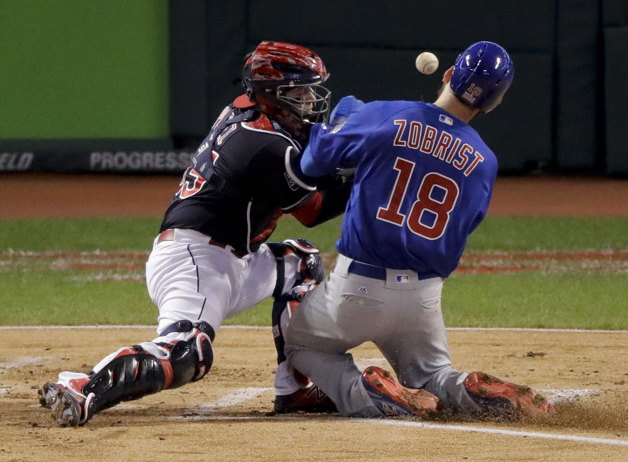 Chicago Cubs' Ben Zobrist scores past Cleveland Indians' Roberto Perez on a double by Addison Russell: during the first inning of Game 6 of the Major League Baseball World Series Tuesday, Nov. 1, 2016, in Cleveland. (AP Photo/Charlie Riedel)