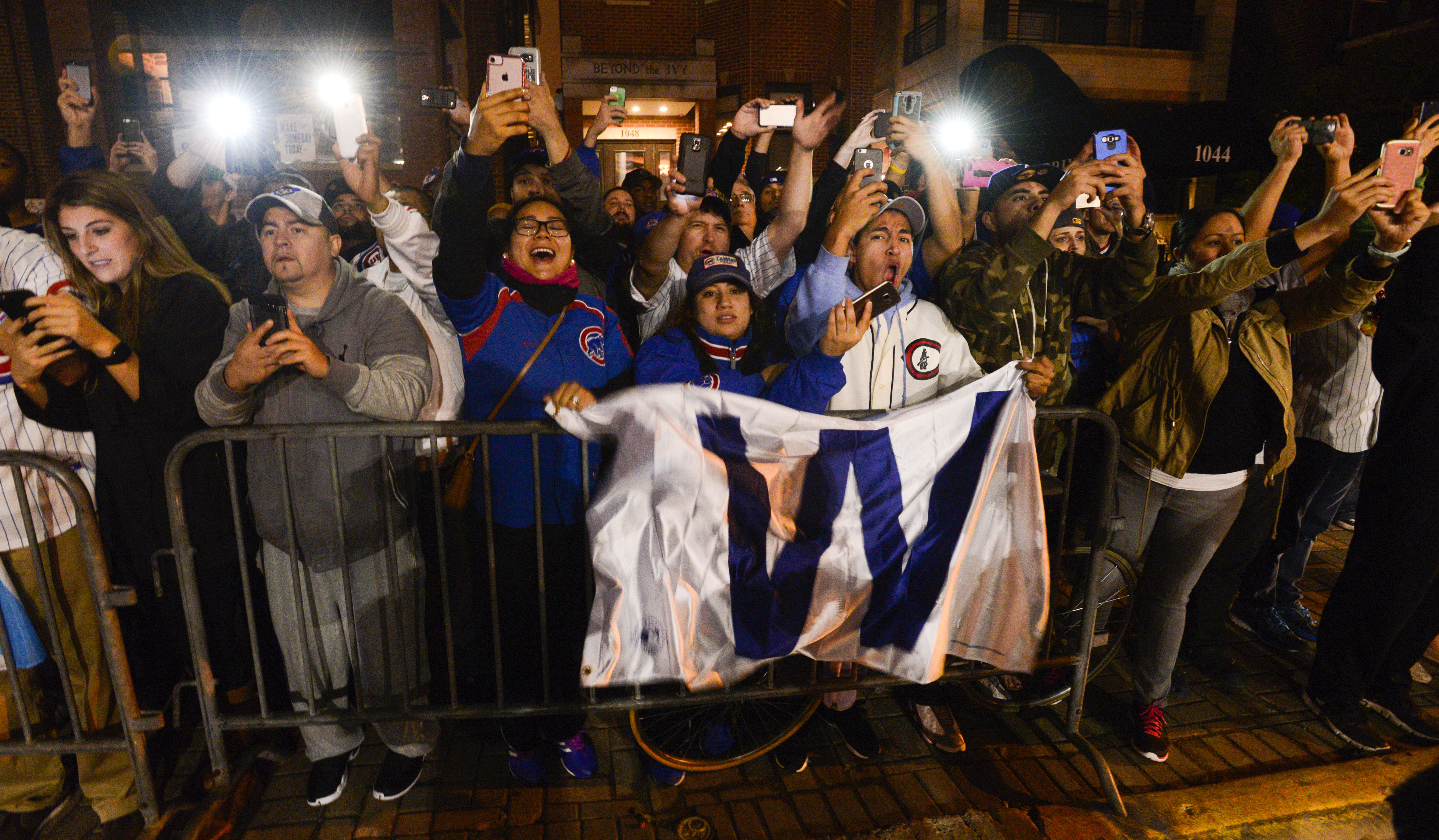 Fans celebrate outside Wrigley Field as buses carrying the Chicago Cubs baseball team arrive in Chicago early Thursday, Nov. 3, 2016, after the Cubs defeated the Cleveland Indians 8-7 in Game 7 of the World Series in Cleveland. (AP Photo/Matt Marton)