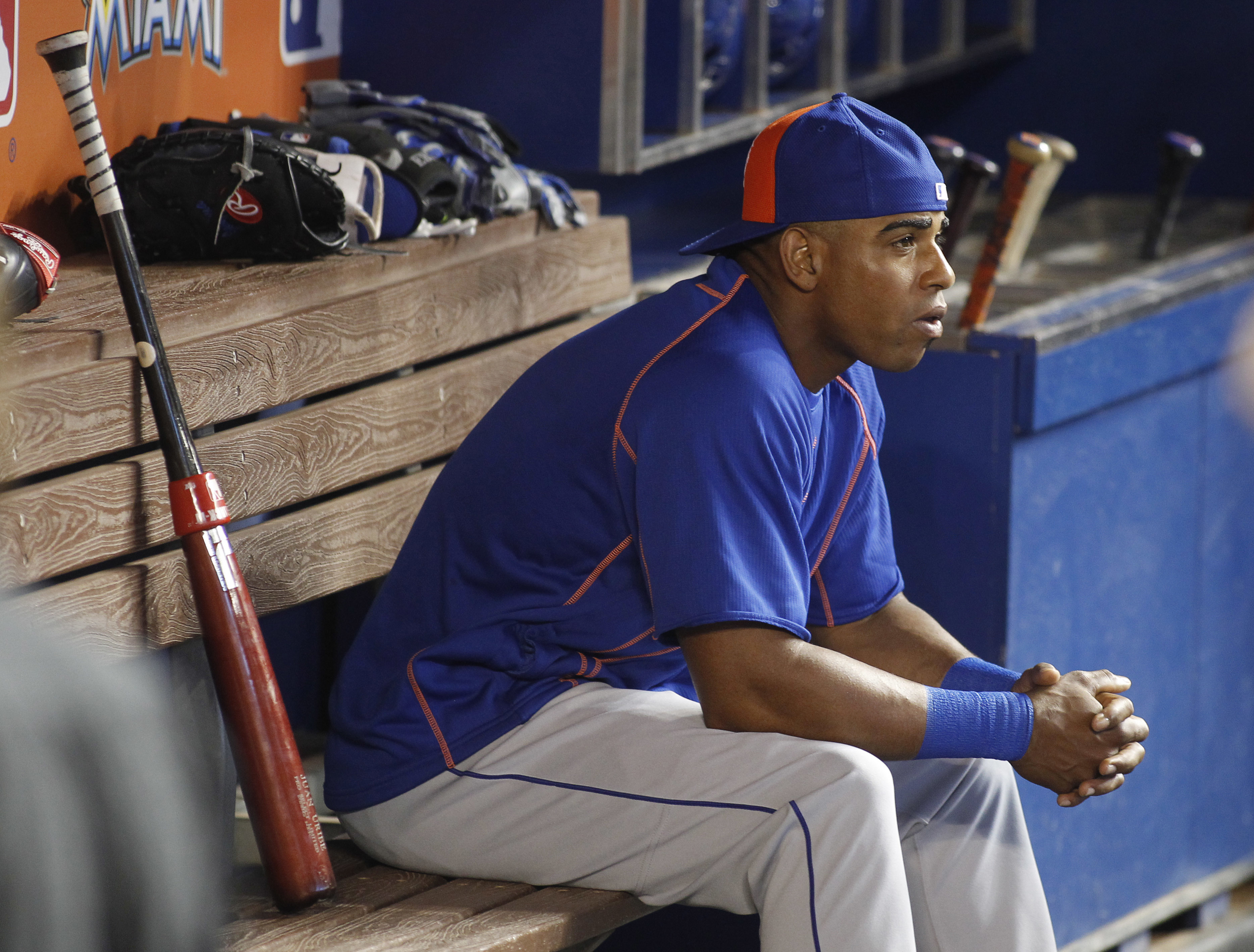 FILE - In this Aug. 5, 2016, file photo, New York Mets center fielder Yoenis Cespedes sits in the dugout before batting practice at a baseball game against the Miami Marlins in Miami. Cespedes is among 10 players to receive $17.2 million qualifying offers