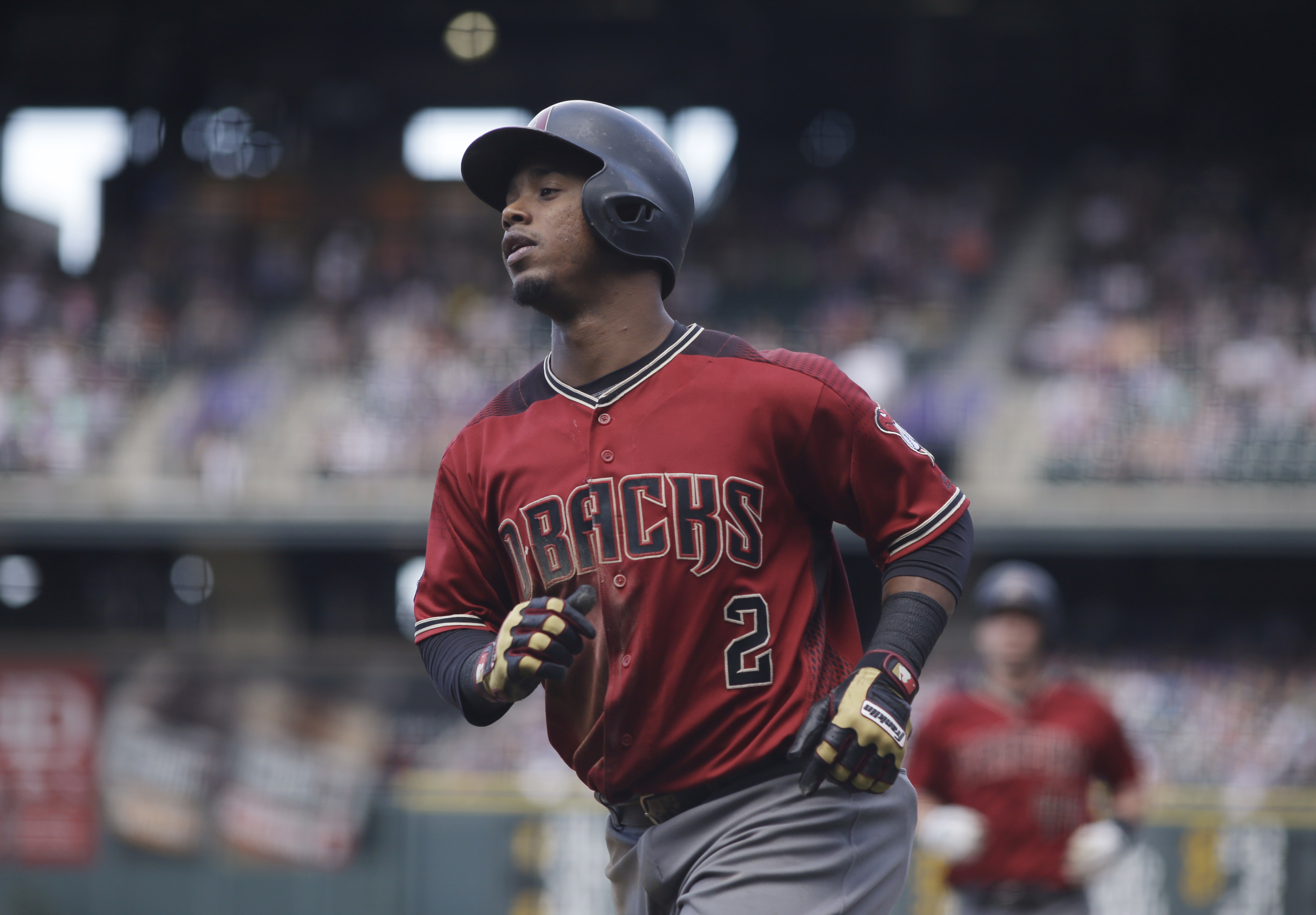FILE - In this Sept. 4, 2016, file photo, Arizona Diamondbacks' Jean Segura heads back to the dugout after scoring against the Colorado Rockies in a baseball game in Denver. Seattle and Arizona pulled off a five-player trade Wednesday night, Nov. 23, with