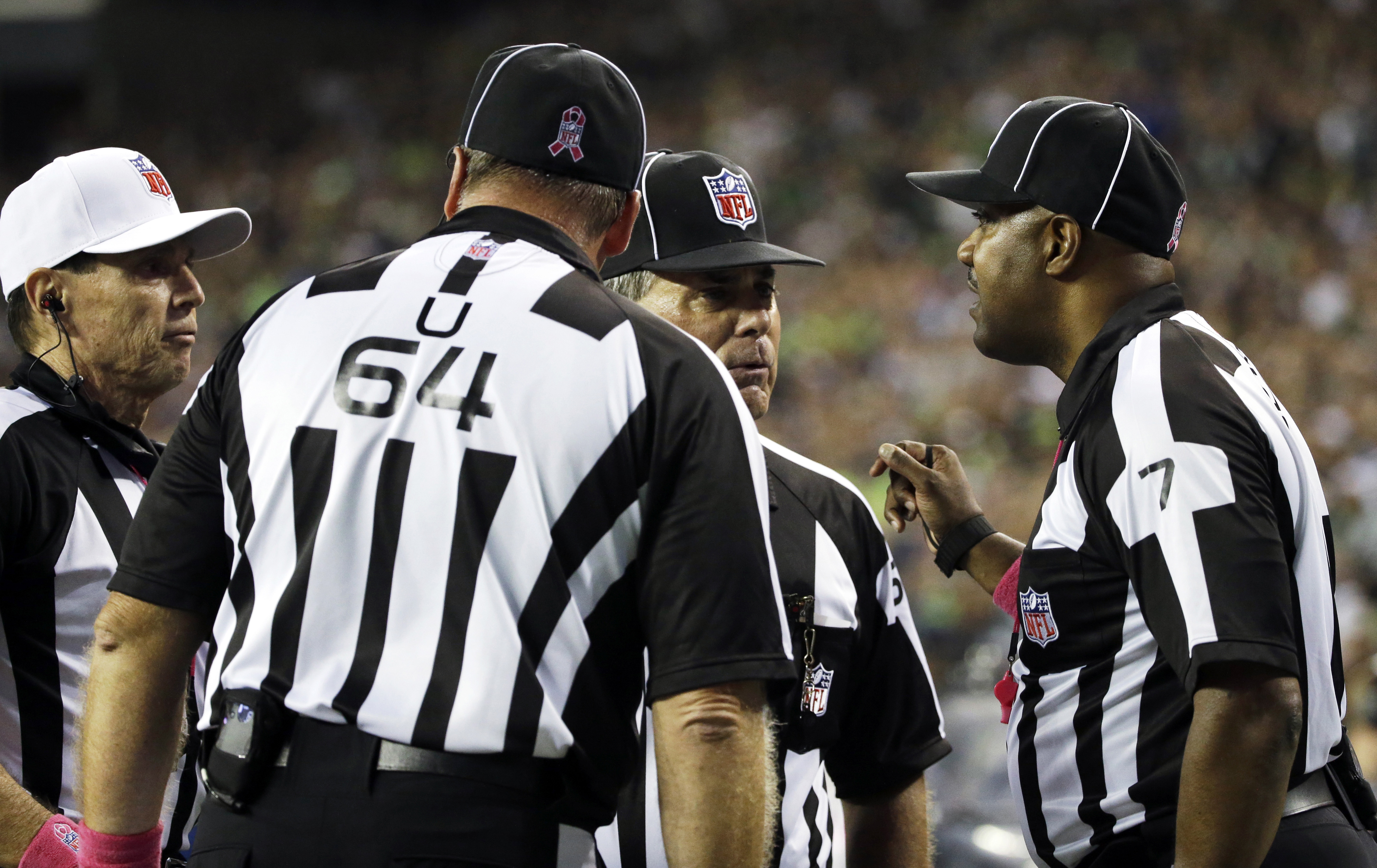 FILE - In this Oct. 5, 2015, file photo, officials, including side judge Keith Washington, right, discuss a play late in the fourth quarter of an NFL football game in Seattle, where a fumble by Detroit Lions wide receiver Calvin Johnson went out of the ba