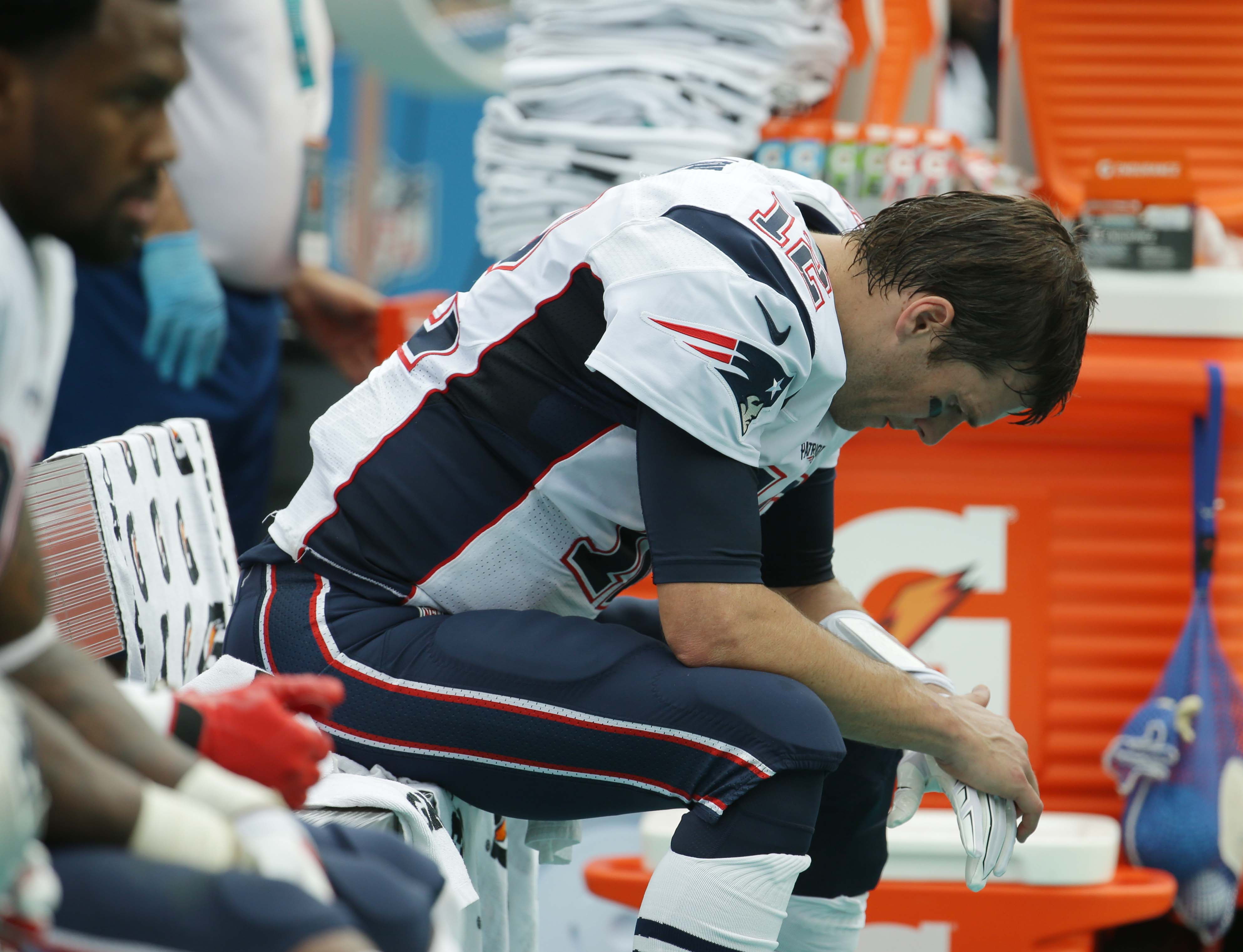 New England Patriots quarterback Tom Brady (12) sits in the sidelines during the first half of an NFL football game against the Miami Dolphins, Sunday, Jan. 3, 2016 in Miami Gardens, Fla. (AP Photo/Lynne Sladky)
