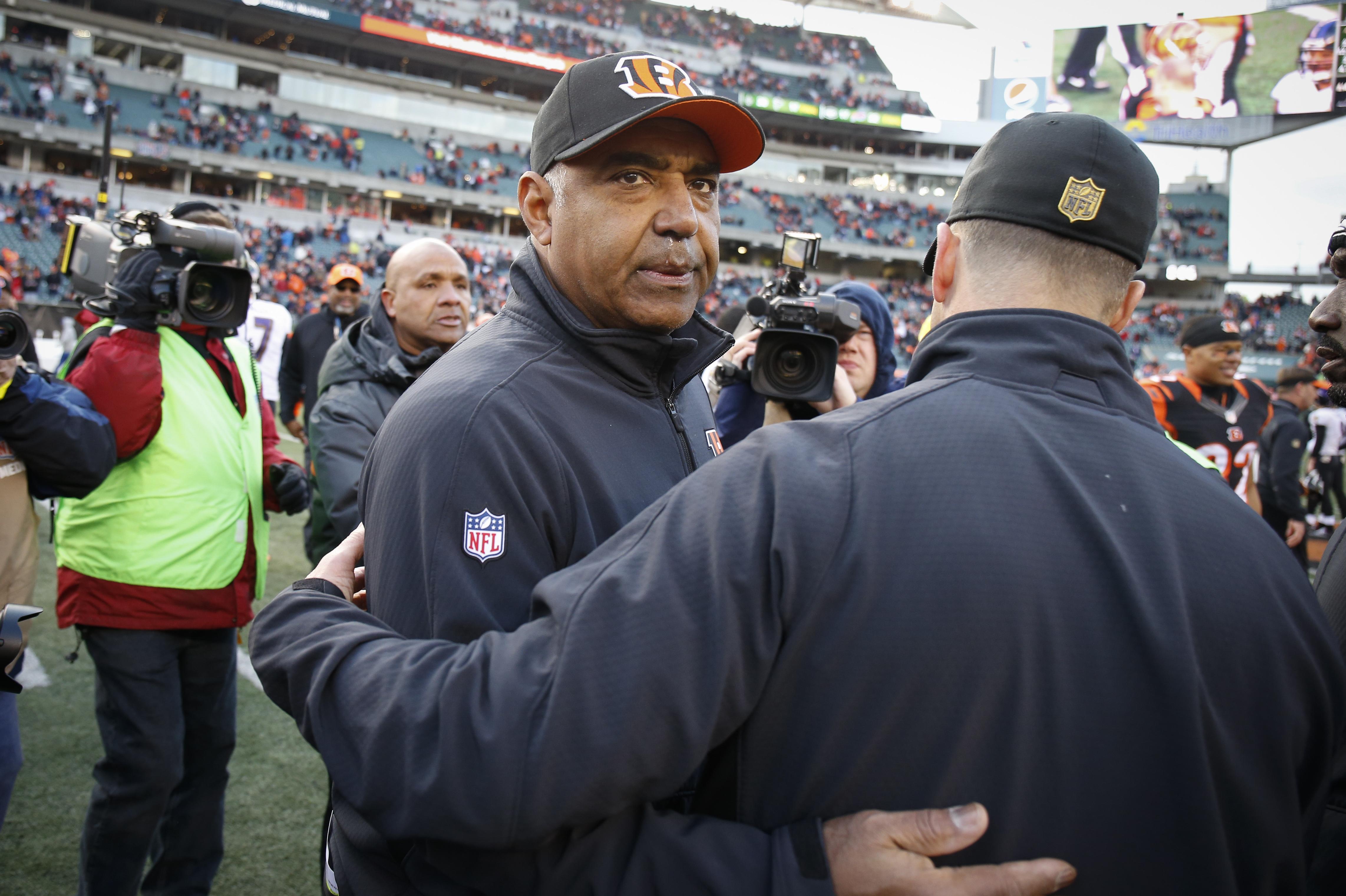 Cincinnati Bengals head coach Marvin Lewis meets with Baltimore Ravens head coach John Harbaugh, right, after an NFL football game, Sunday, Jan. 3, 2016, in Cincinnati. Cincinnati won 24-16. (AP Photo/Gary Landers)