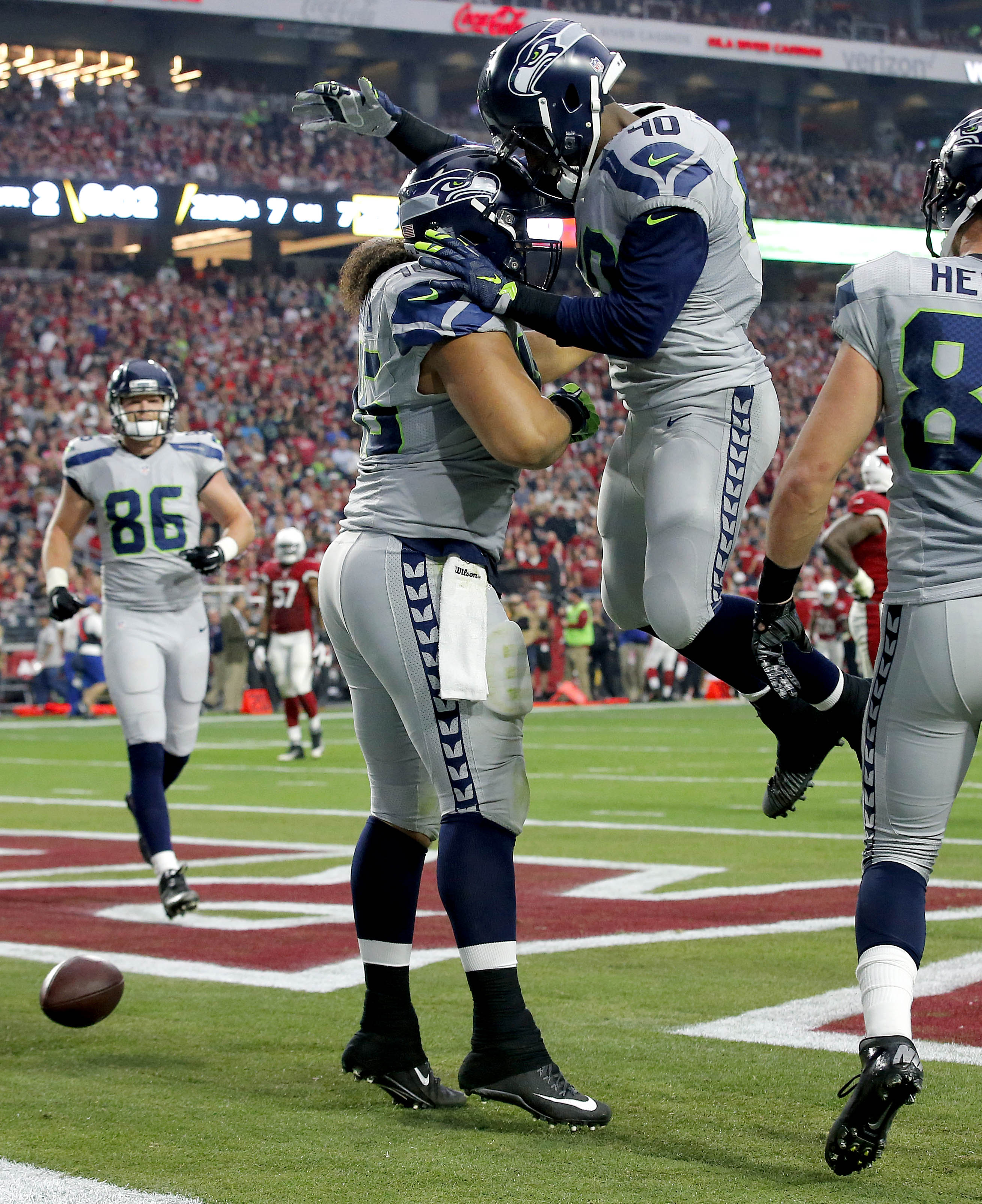 Seattle Seahawks fullback Will Tukuafu (46) celebrates with teammate Derrick Coleman (40) after scoring a touchdown against the Arizona Cardinals during the first half of an NFL football game, Sunday, Jan. 3, 2016, in Glendale, Ariz. (AP Photo/Ross D. Fra