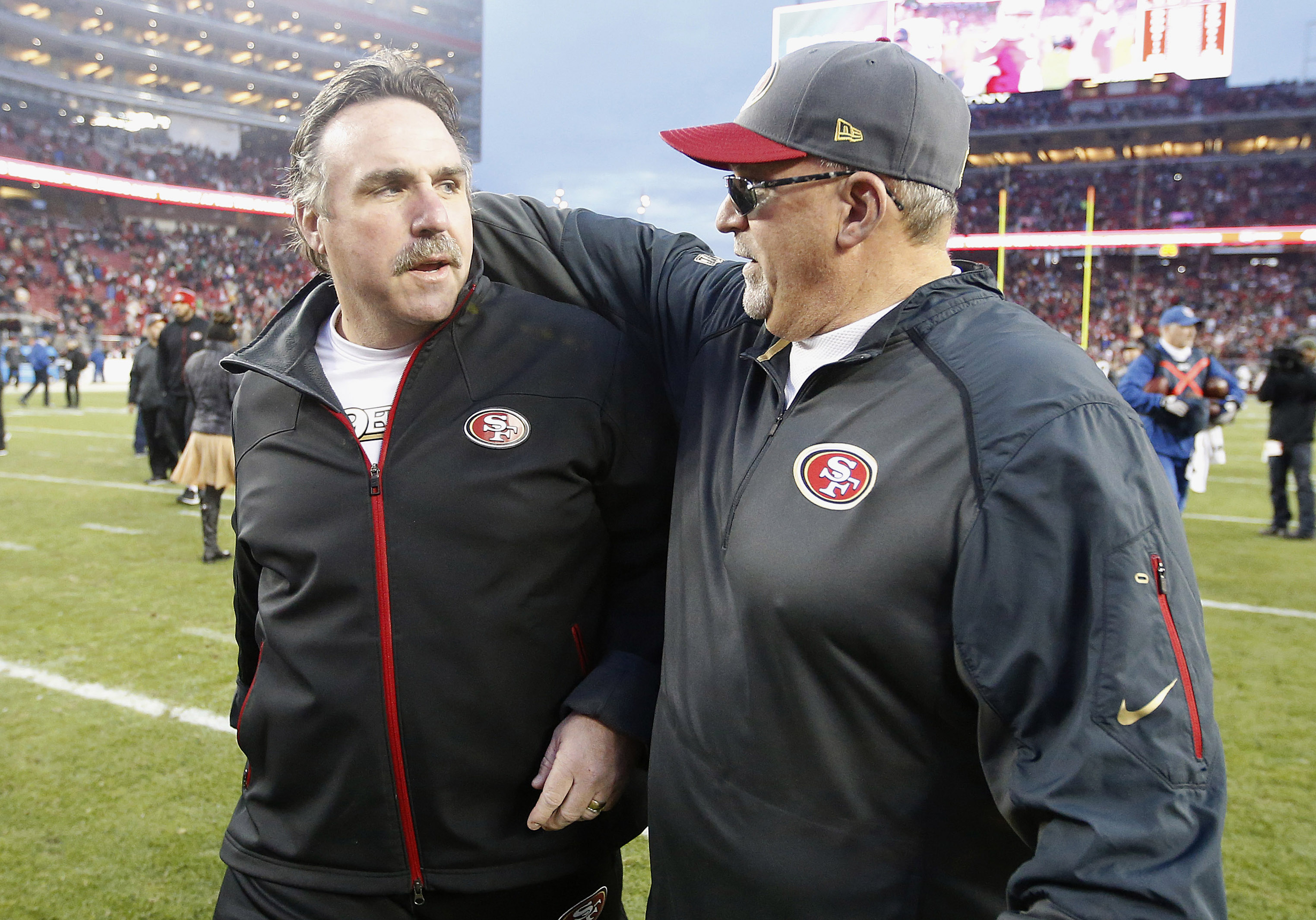 San Francisco 49ers head coach Jim Tomsula, left, walks off the field with tight ends coach Tony Sparano after an NFL football game against the St. Louis Rams in Santa Clara, Calif., Sunday, Jan. 3, 2016. The 49ers won 19-16 in overtime. (AP Photo/Tony Av