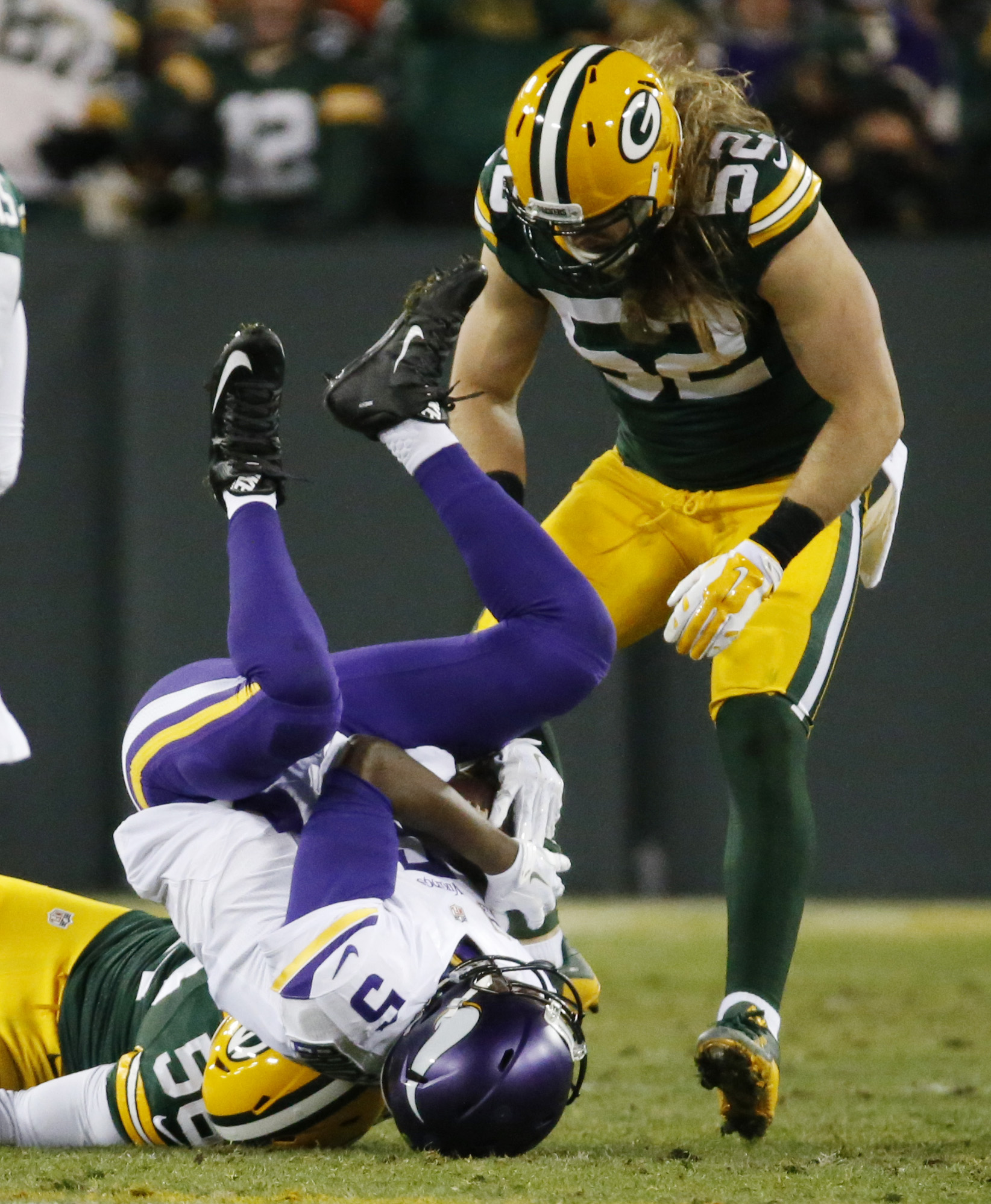 Minnesota Vikings' Teddy Bridgewater is stopped by Green Bay Packers' Julius Peppers and Clay Matthews (52) on a run during the first half an NFL football game Sunday, Jan. 3, 2016, in Green Bay, Wis. (AP Photo/Mike Roemer)