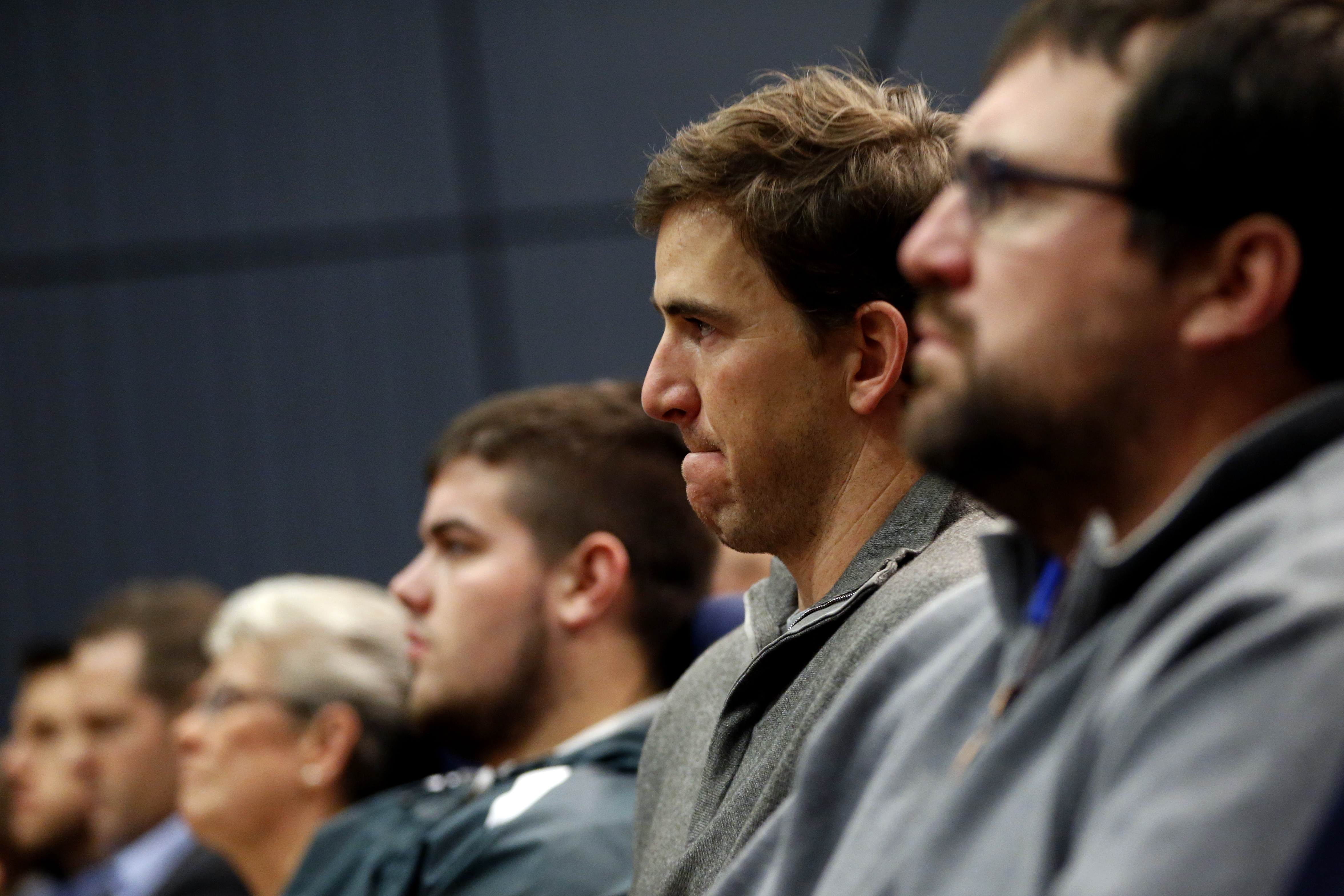 New York Giants quarterback Eli Manning, center, reacts while listening to former head coach Tom Coughlin speak during a news conference, Tuesday, Jan. 5, 2016, in East Rutherford, N.J. (AP Photo/Julio Cortez)