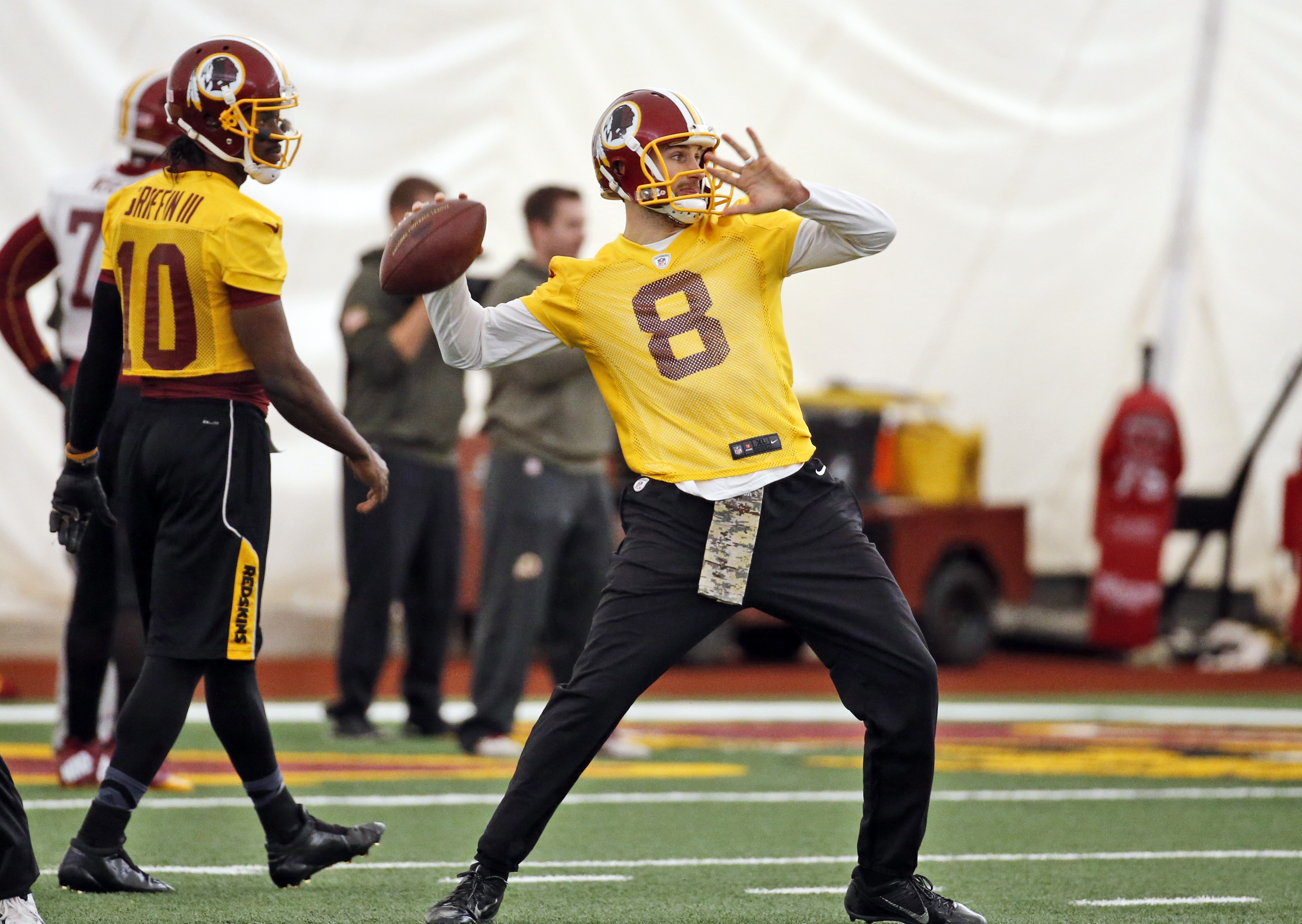 Washington Redskins quarterback Robert Griffin III (10) watches as quarterback Kirk Cousins (8) throws the ball during practice at the team's NFL football training facility at Redskins Park, Thursday, Jan. 7, 2016 in Ashburn, Va. The Washington Redskins w