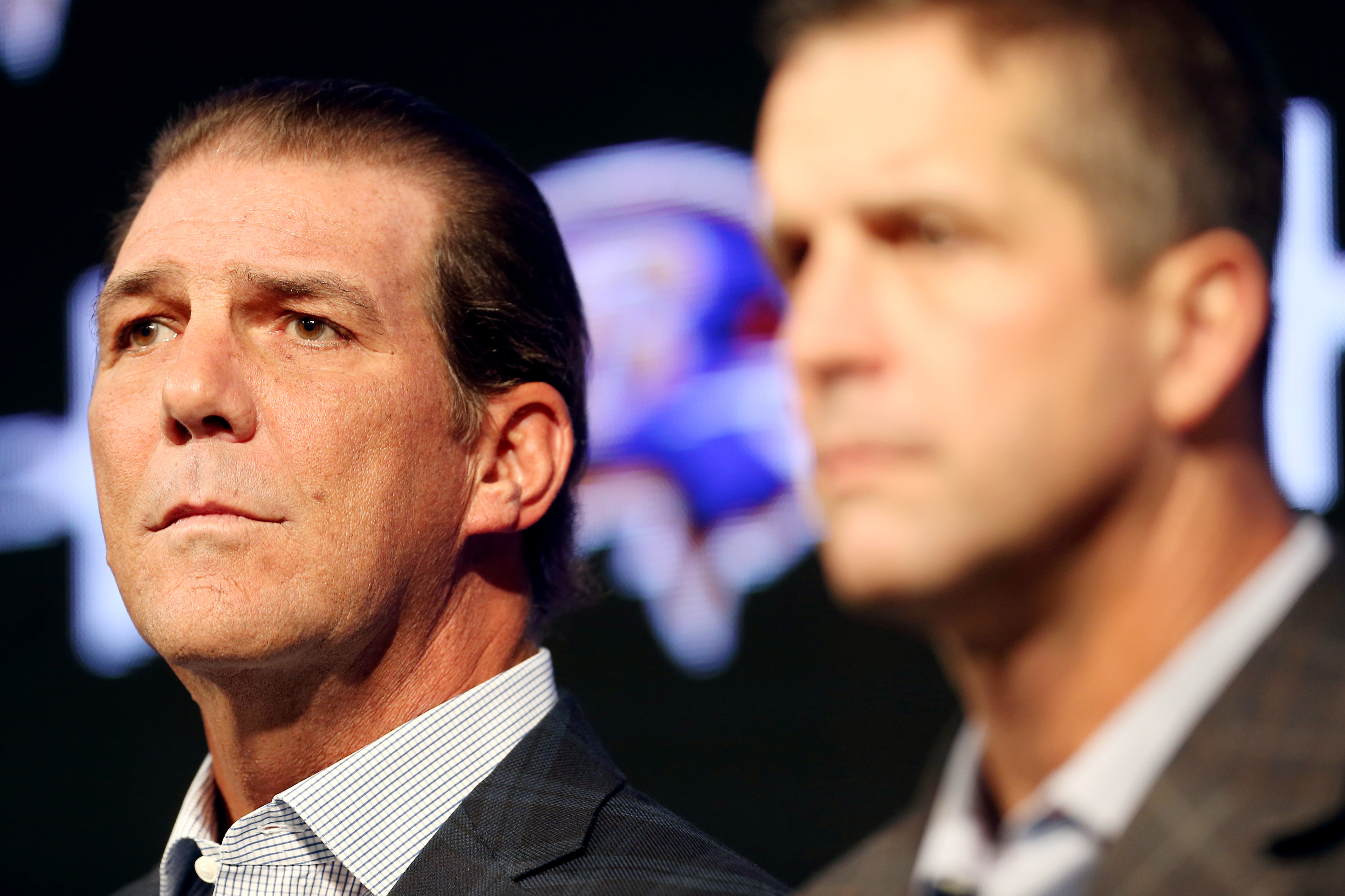 Baltimore Ravens owner Steve Bisciotti, left, listens to a reporter's question as he sits next to head coach John Harbaugh during an NFL football news conference at the team's practice facility in Owings Mills, Md., Thursday, Jan. 7, 2016. The team held t