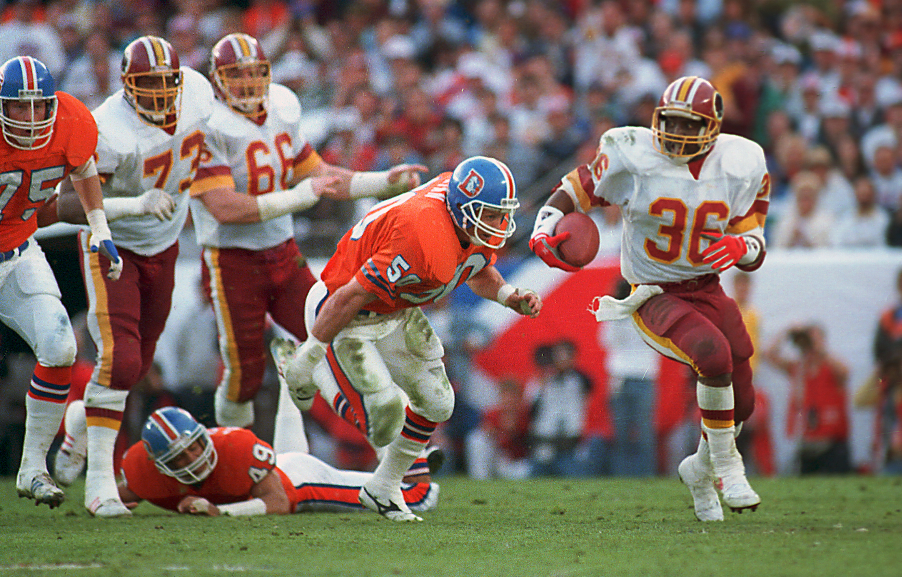 FILE - In this Jan. 31, 1988, file photo, Washington Redskins running back Timmy Smith (36) goes around Denver Broncos linebacker Jim Ryan (50) on a long run in the first quarter of NFL football's Super Bowl XXII in San Diego. Smith ran for a record 204 y