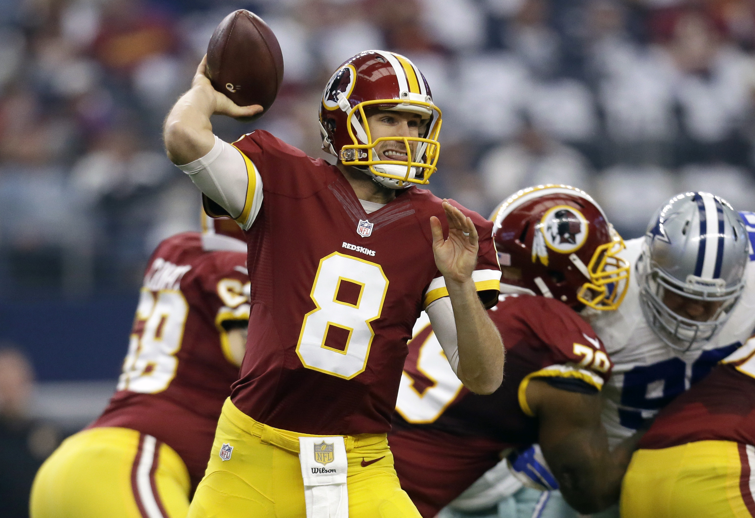 FILE - In this Sunday, Jan. 3, 2016, file photo, Washington Redskins quarterback Kirk Cousins (8) looks to pass under pressure in the first half of an NFL football game against the Dallas Cowboys in Arlington, Texas. Cousins has soared, breaking team pass