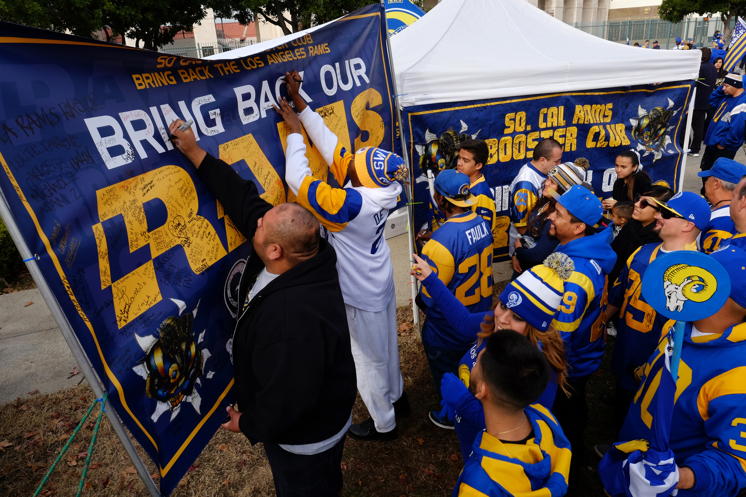 Rams fans sign a banner in support of their team at the historic Los Angeles Memorial Coliseum. Saturday, Jan. 9, 2016 in Los Angeles. Boisterous Los Angeles Rams fans gathered Saturday to herald the NFL football team's possibly imminent return to Souther