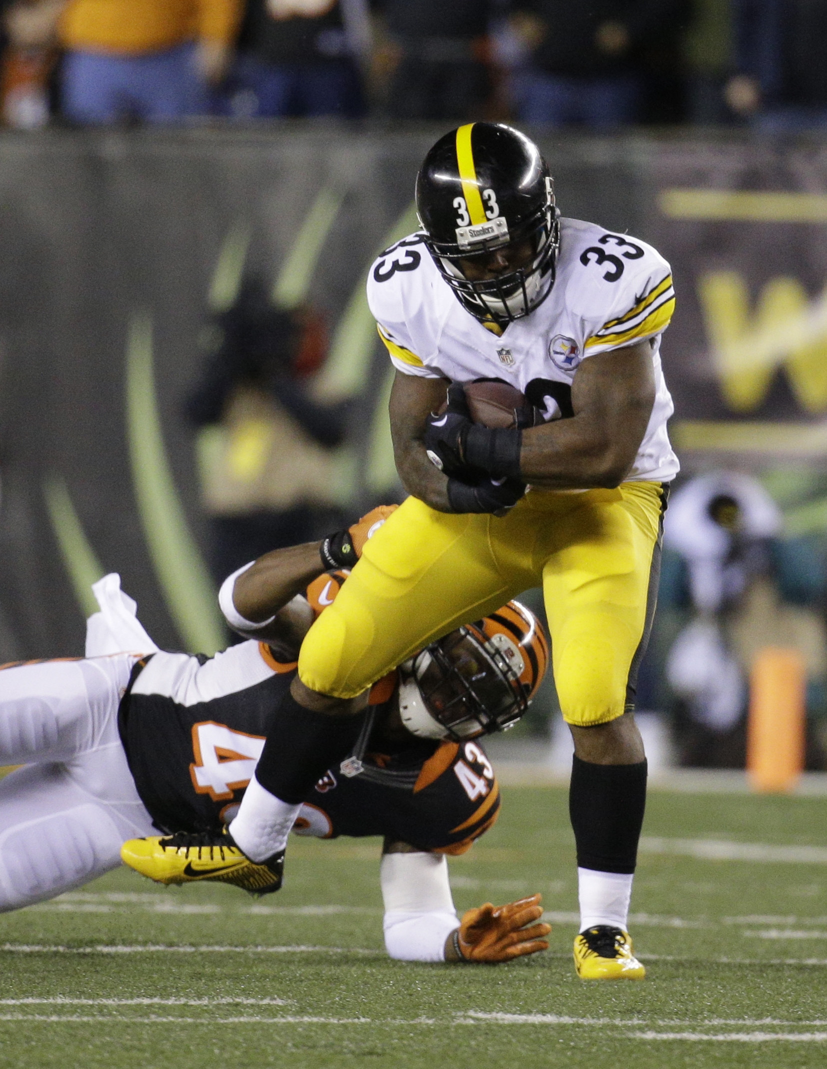 Pittsburgh Steelers' Fitzgerald Toussaint (33) is tackled by Cincinnati Bengals' George Iloka (43) during the first half of an NFL wild-card playoff football game Saturday, Jan. 9, 2016, in Cincinnati. (AP Photo/John Minchillo)