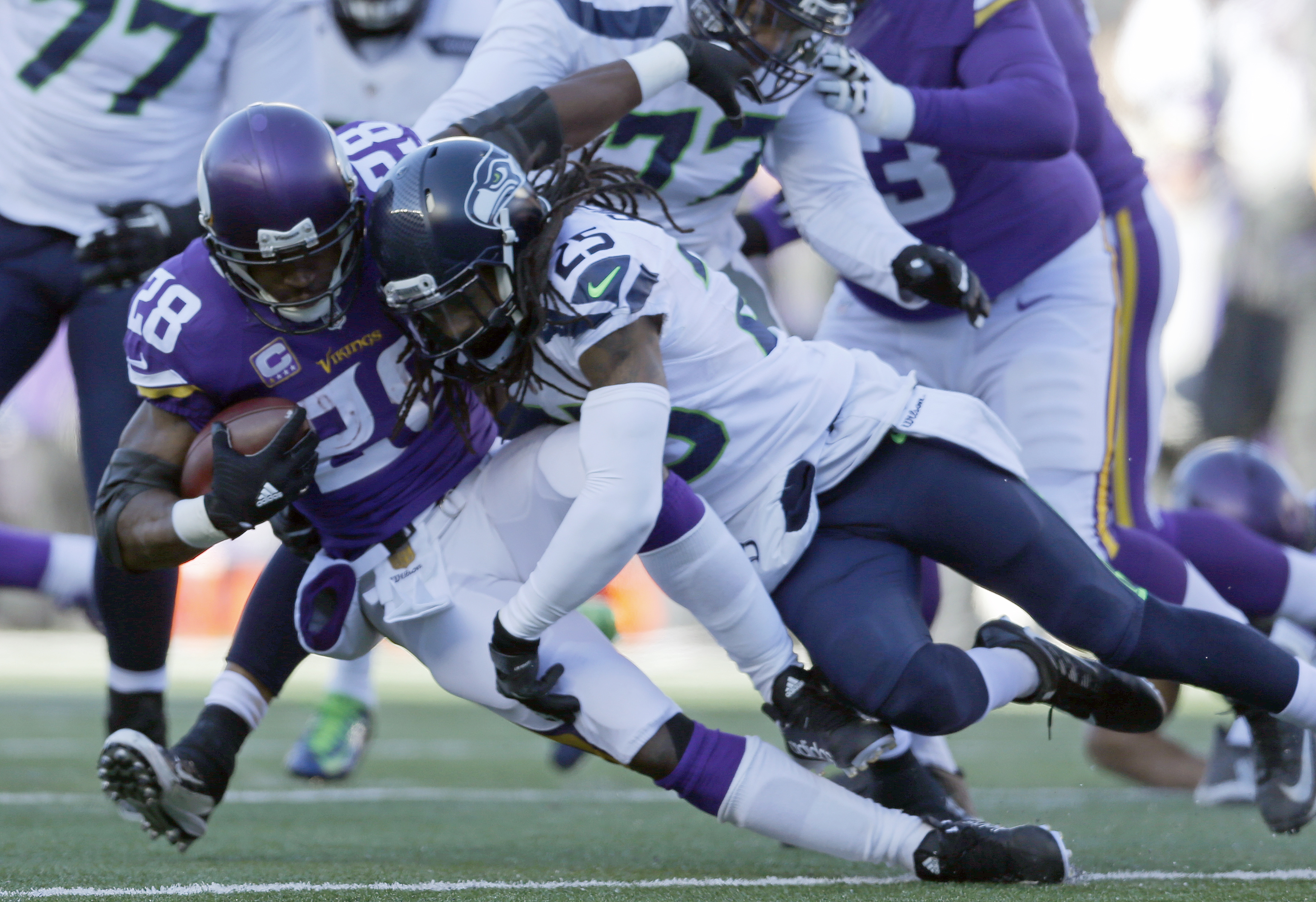 Minnesota Vikings running back Adrian Peterson (28) is tacked by Seattle Seahawks cornerback Richard Sherman (25) during the first half of an NFL wild-card football game, Sunday, Jan. 10, 2016, in Minneapolis. (AP Photo/Kiichiro Sato)