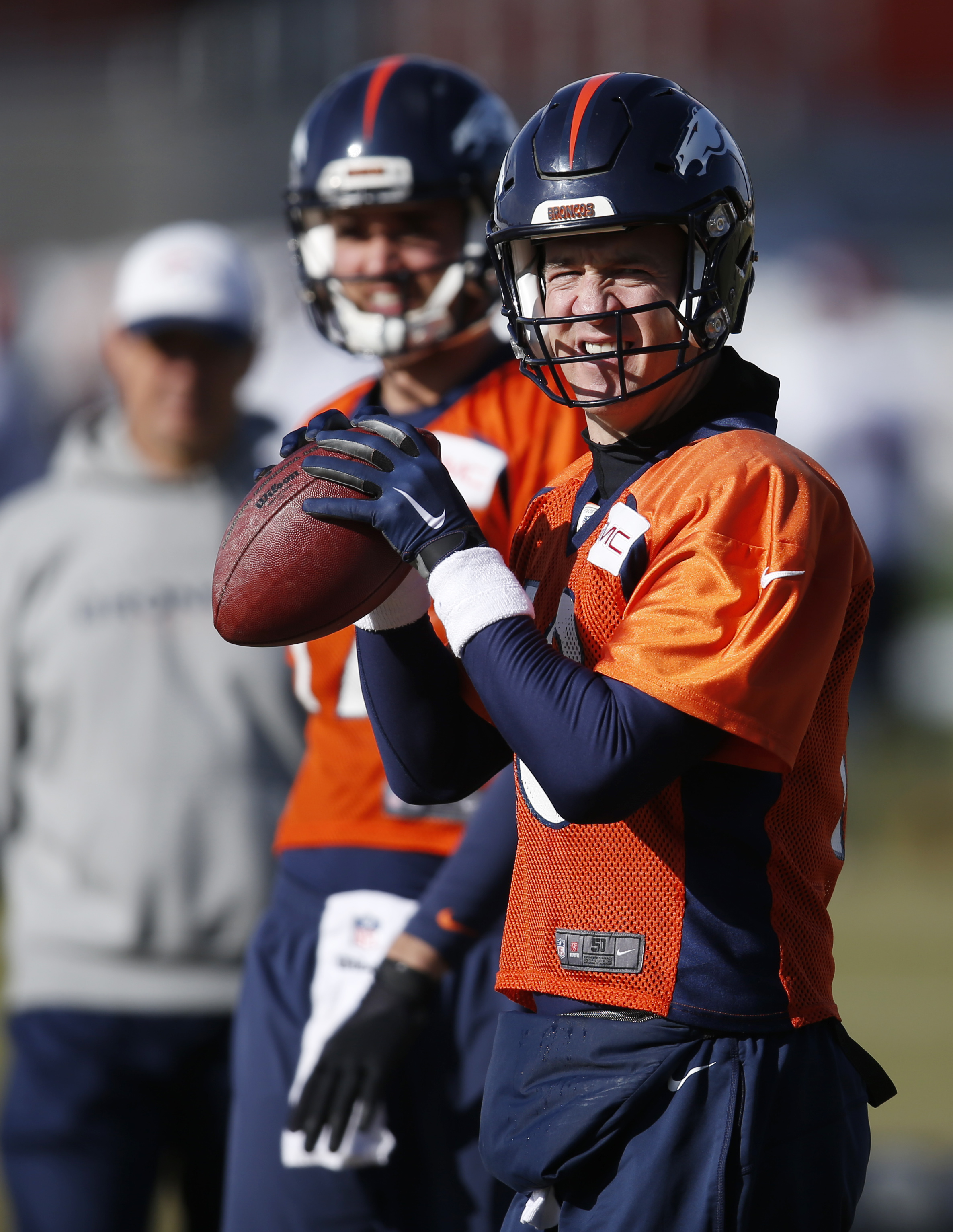 Denver Broncos quarterback Peyton Manning, front, warms up as backup quarterback Brock Osweiler looks on during an NFL football practice at the team's headquarters Wednesday, Jan. 13, 2016, in Englewood, Colo. The Broncos will host the Pittsburgh Steelers