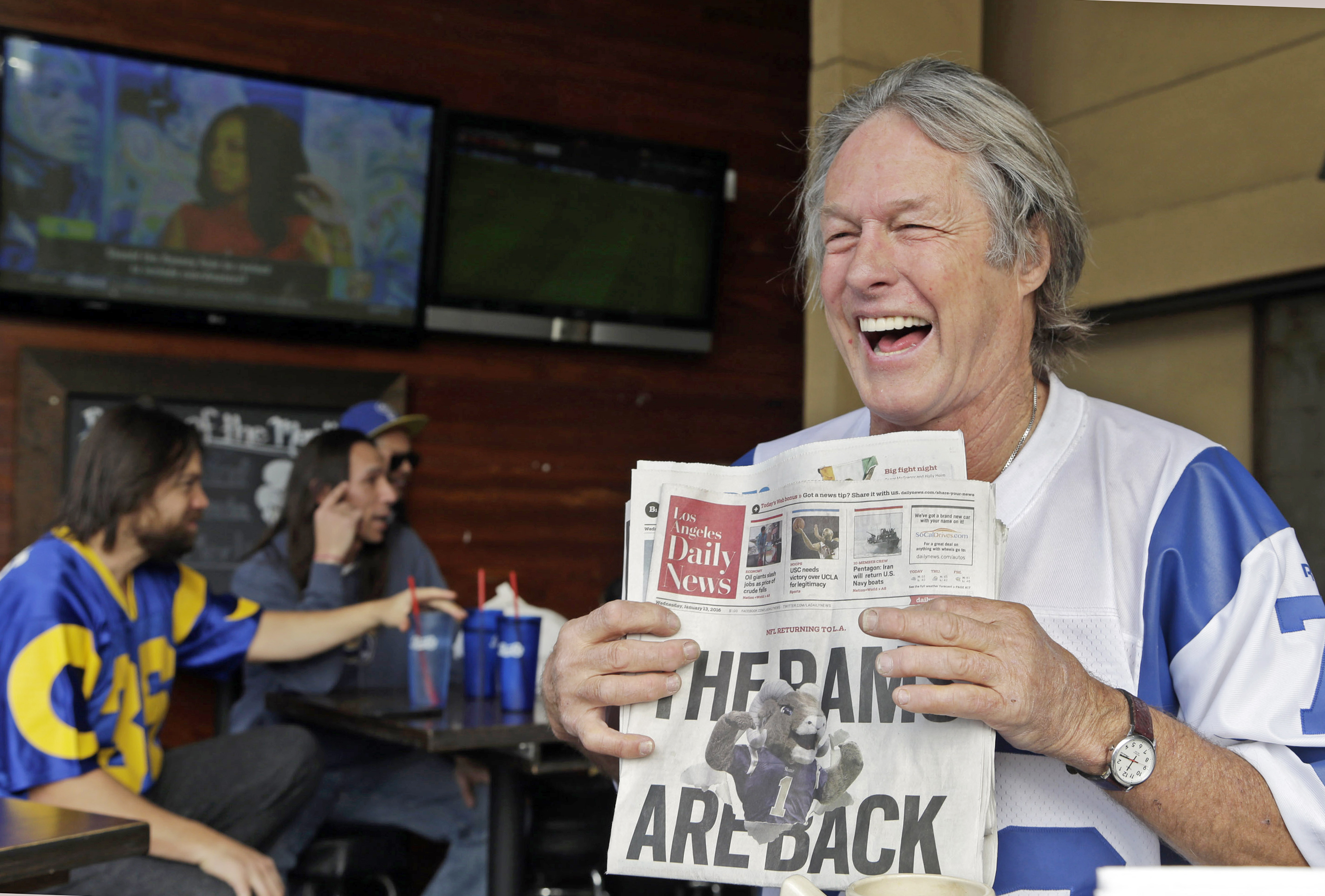 Rams fan Don Kirst holds a copy of the Los Angeles Daily News celebrating the impending return of the NFL football team to the Los Angeles area, at Big Wangs sports bar in the North Hollywood area of Los Angeles on Wednesday, Jan. 13, 2016. League owners