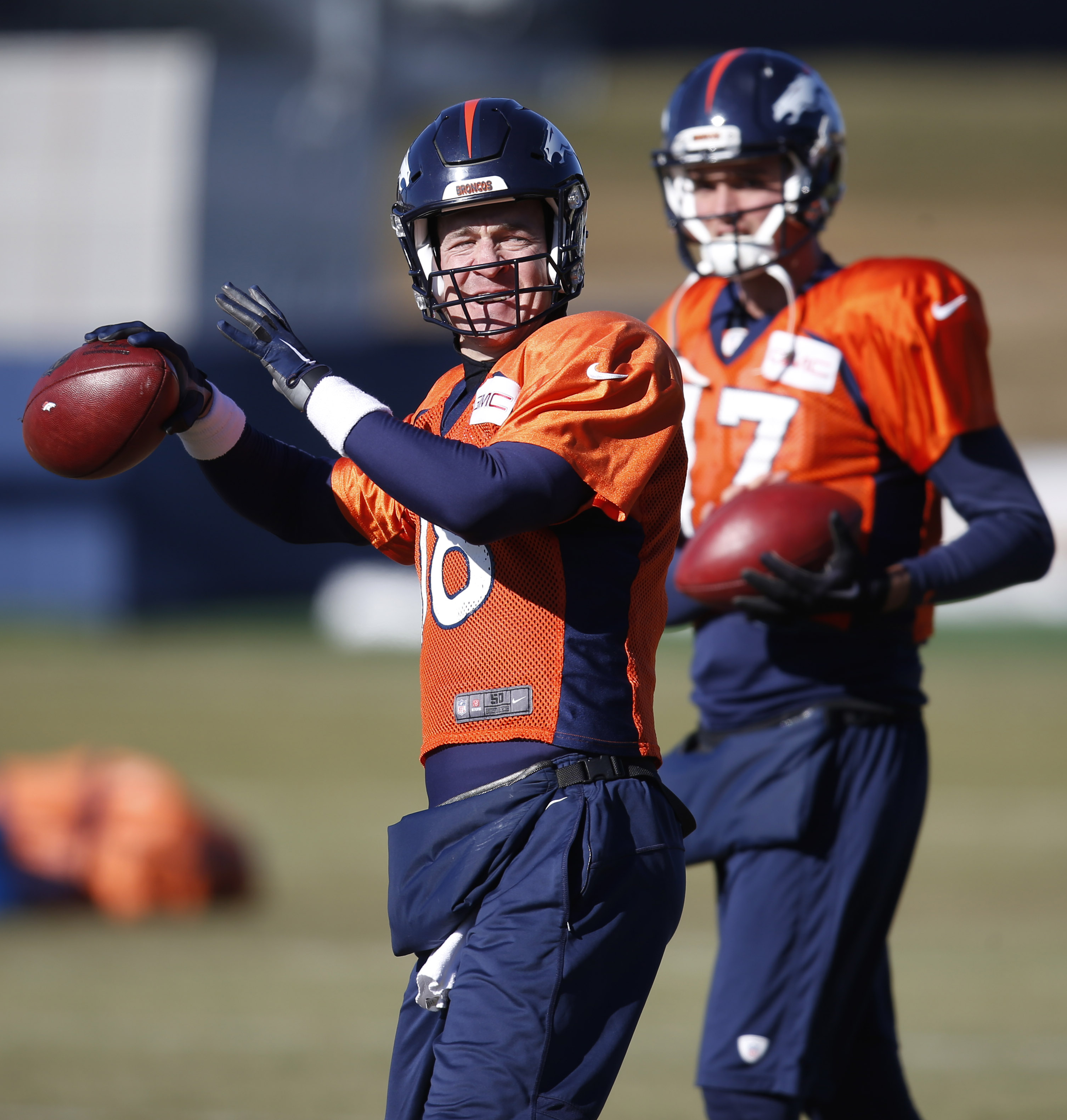 Denver Broncos quarterback Peyton Manning, front, throws a pass as backup quarterback Brock Osweiler looks on during an NFL football practice Thursday, Jan. 14, 2016, in Englewood, Colo. The Broncos are preparing for their divisional round AFC playoff gam