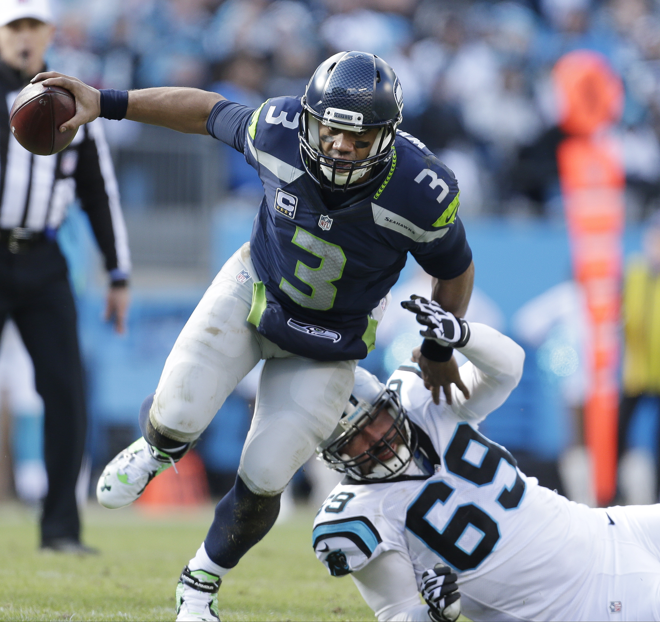 Seattle Seahawks quarterback Russell Wilson (3) runs by Carolina Panthers defensive end Jared Allen (69) during the first half of an NFL divisional playoff football game, Sunday, Jan. 17, 2016, in Charlotte, N.C. (AP Photo/Bob Leverone)