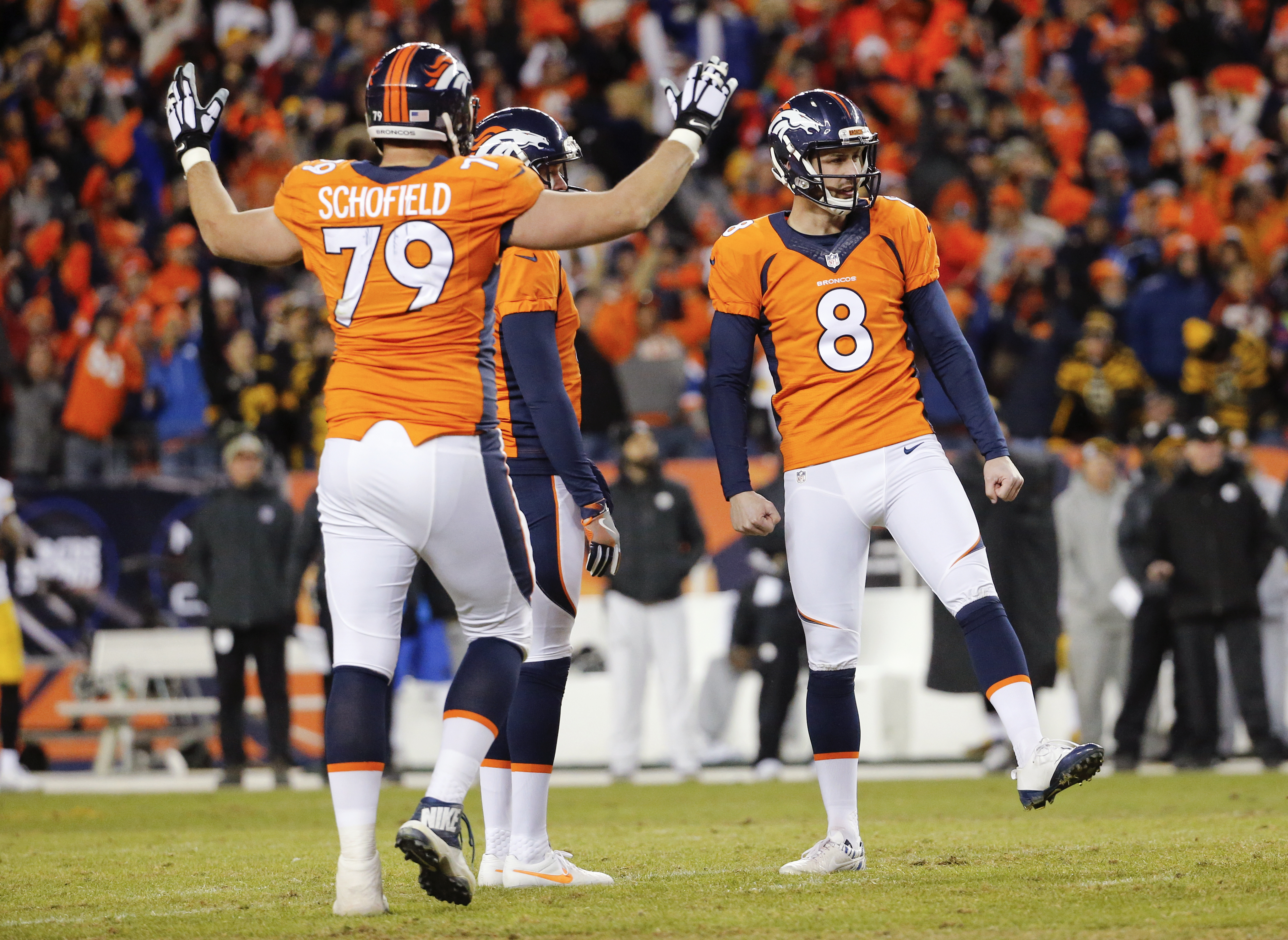Denver Broncos kicker Brandon McManus, right, celebrates after kicking a field goal with tackle Michael Schofield, left, and Britton Colquitt, center, during the second half in an NFL football divisional playoff game, Sunday, Jan. 17, 2016, in Denver. (AP