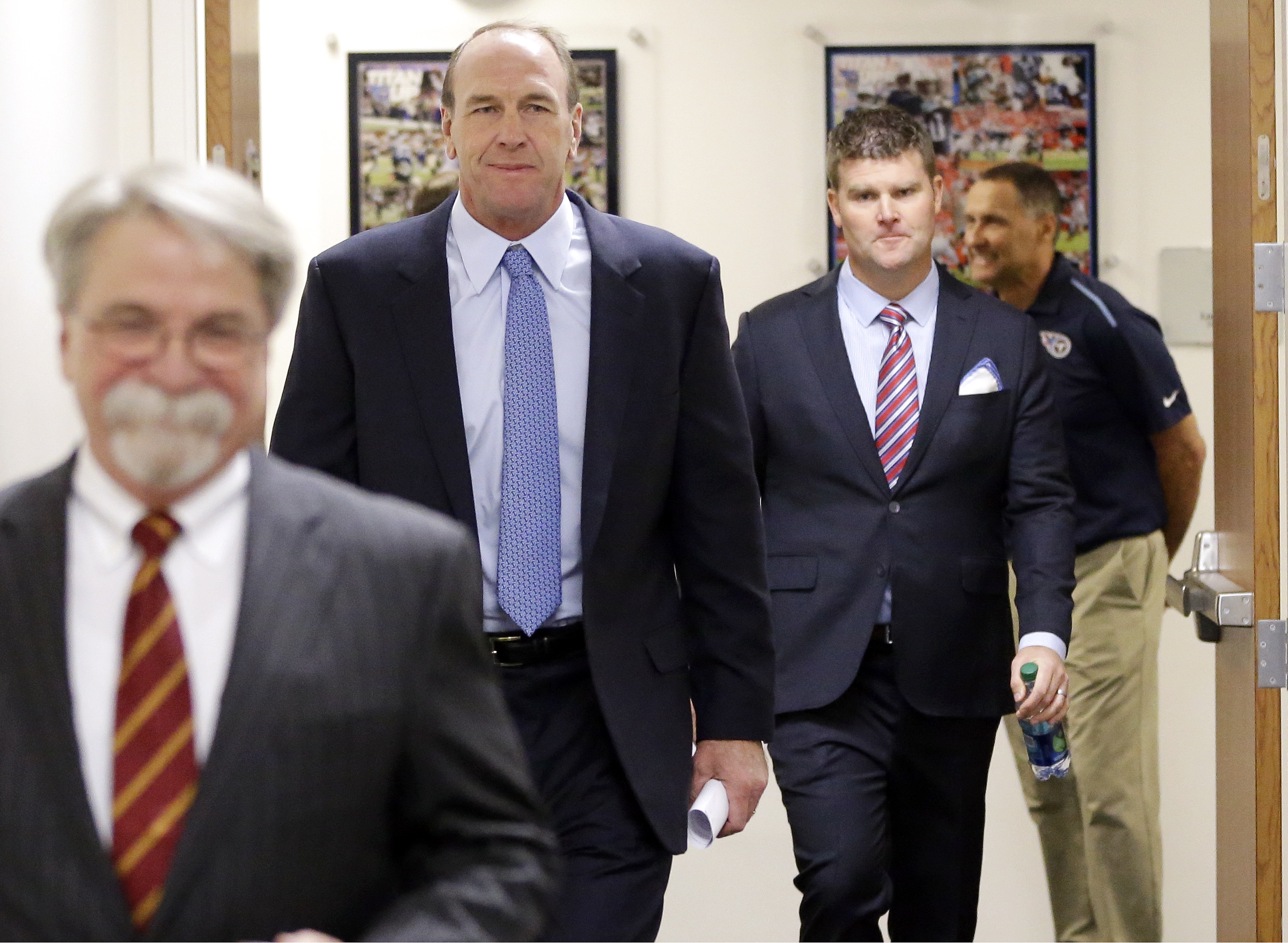 Recently hired Tennessee Titans head coach Mike Mularkey, second from left, and general manager Jon Robinson, second from right, arrive for a news conference Monday, Jan. 18, 2016, in Nashville, Tenn. Mularkey was previously the team's interim head coach