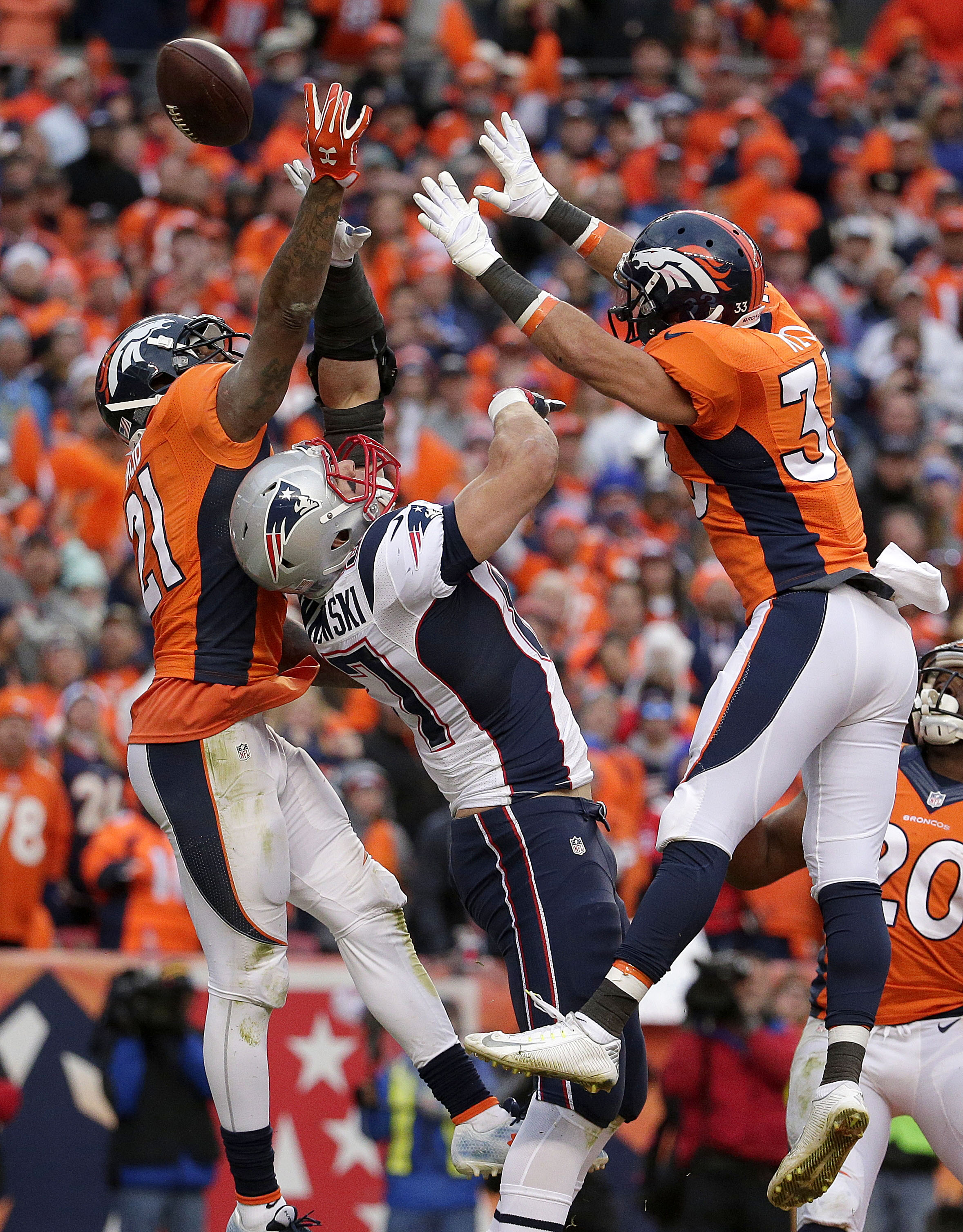 New England Patriots tight end Rob Gronkowski (87) is defended by Denver Broncos cornerback Aqib Talib (21) and defensive back Shiloh Keo during the second half of the NFL football AFC Championship game between the Denver Broncos and the New England Patri