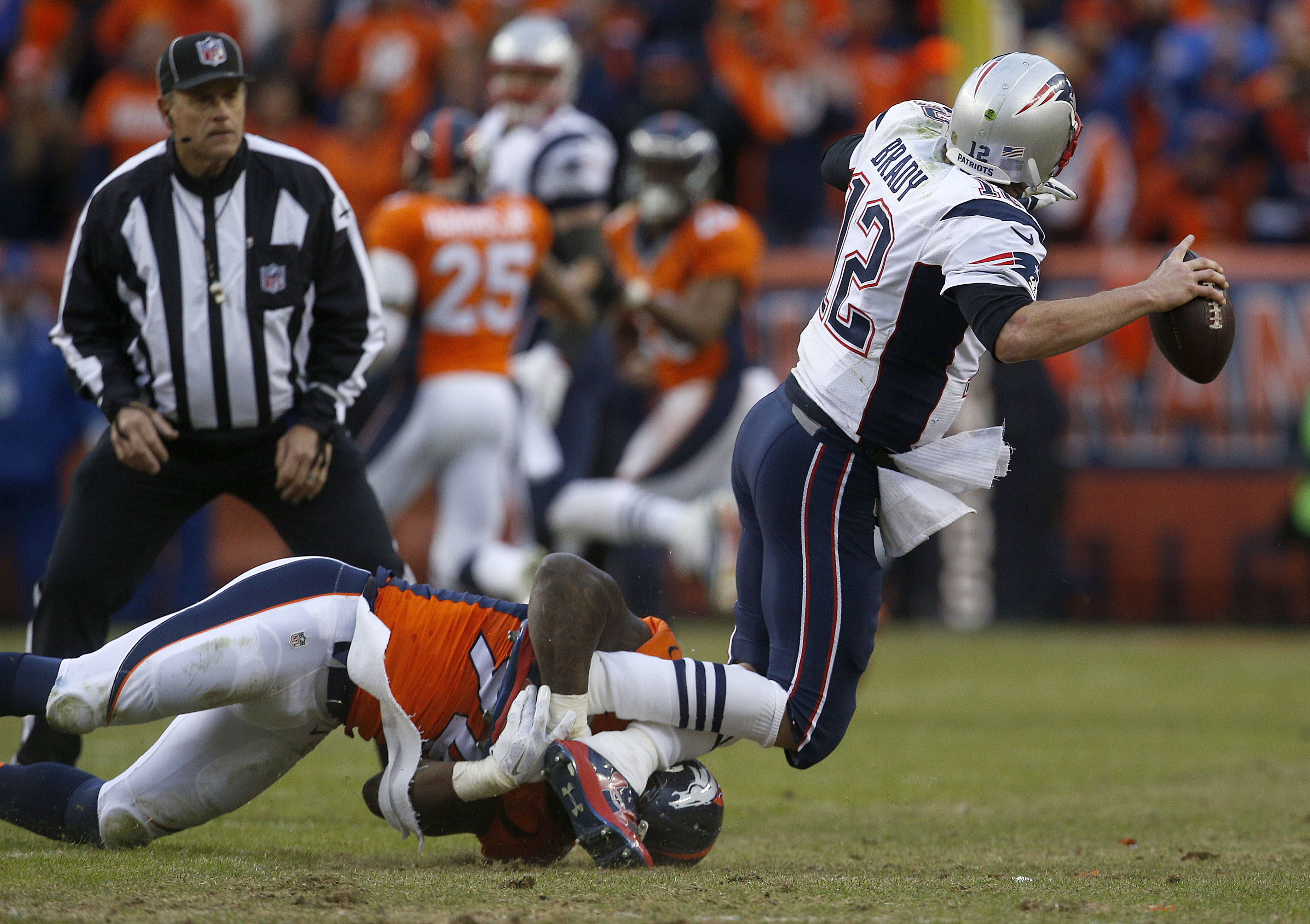 New England Patriots quarterback Tom Brady throws the ball as he is brought down by Denver Broncos outside linebacker DeMarcus Ware during the second half of the AFC Championship game between the Denver Broncos and the New England Patriots, Sunday, Jan. 2