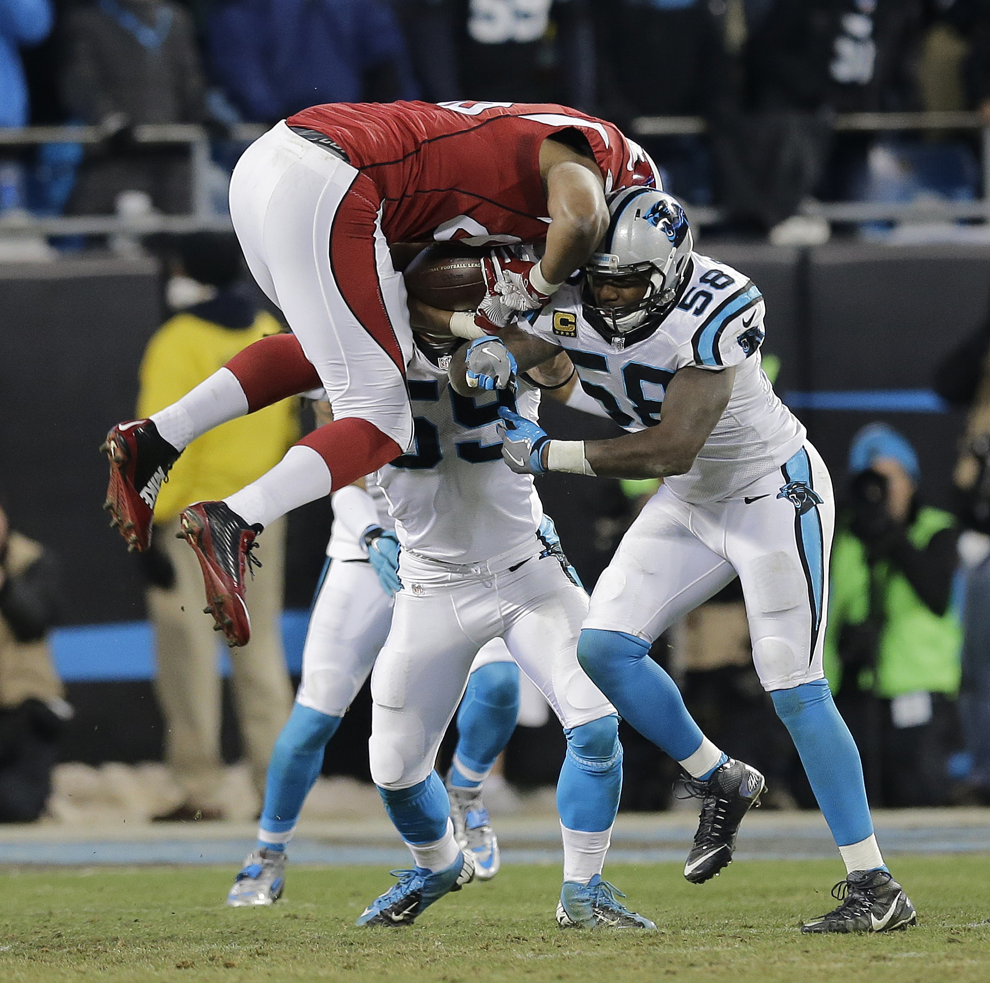 Arizona Cardinals' Darren Fells is hit by Carolina Panthers' Thomas Davis (58) and Luke Kuechly after catching a pass during the first half the NFL football NFC Championship game Sunday, Jan. 24, 2016, in Charlotte, N.C. (AP Photo/David J. Phillip)