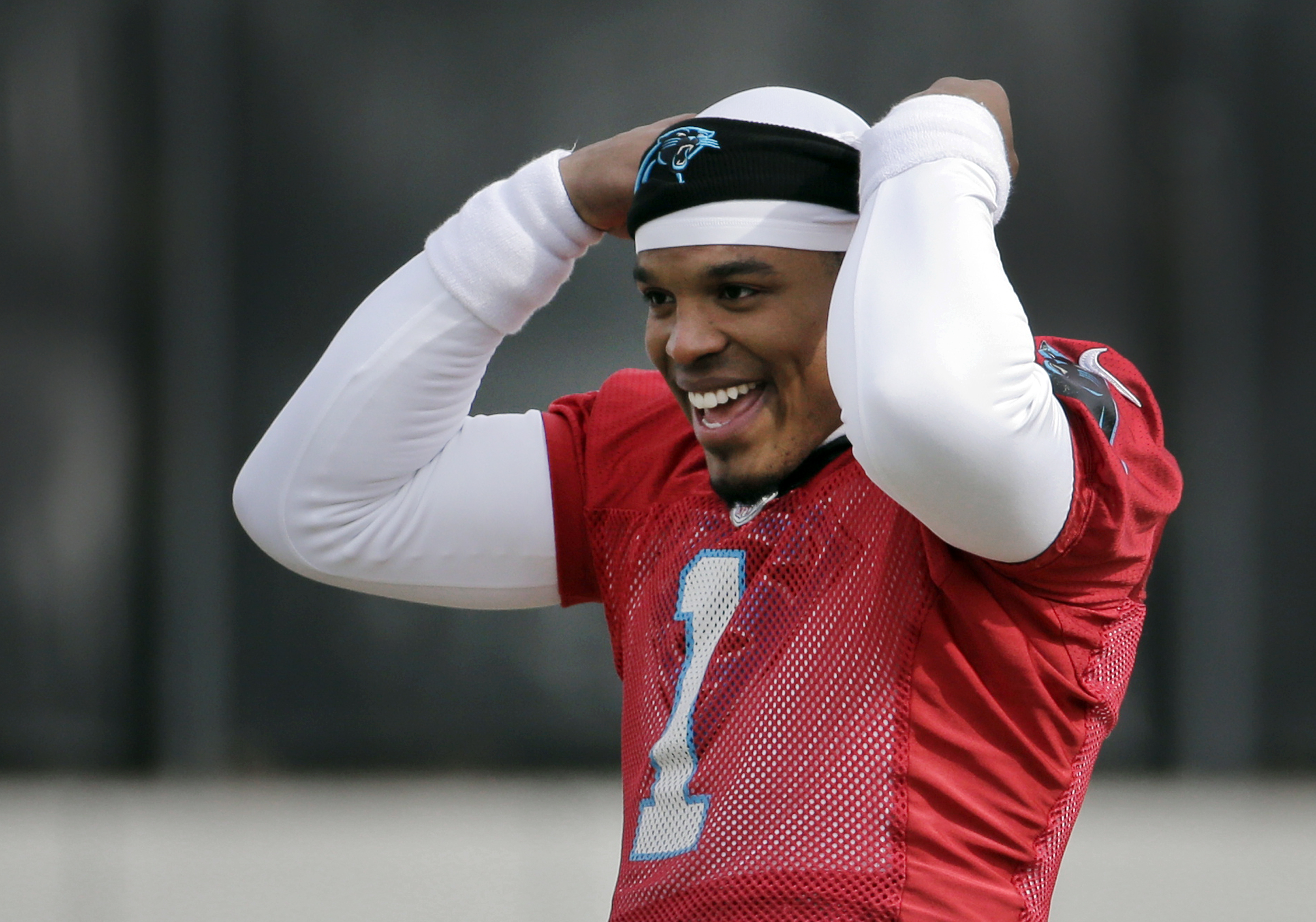 Carolina Panthers quarterback Cam Newton jokes with teammates during practice for the NFL football team in Charlotte, N.C., Wednesday, Jan. 27, 2016.  The Panthers will meet the Denver Broncos in Super Bowl 50 in Santa Clara, Calif., on Feb. 7. (AP Photo/