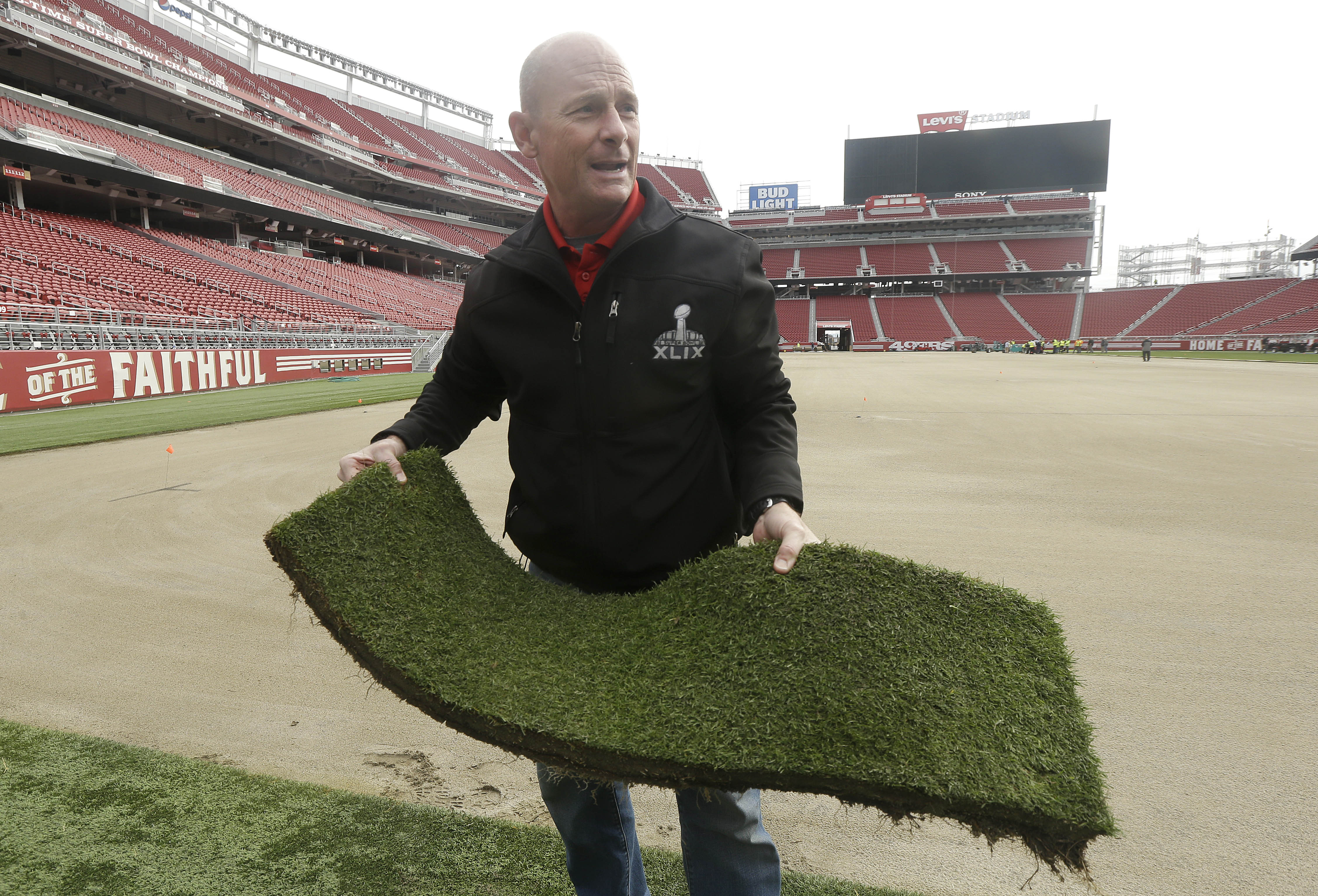 In this photo from Monday, Jan. 11, 2016, NFL field director Ed Mangan holds up a piece of sod as he speaks to reporters about the field preparation for Super Bowl 50 at Levi's Stadium in Santa Clara, Calif. Mangan, working his 27th Super Bowl, oversaw th