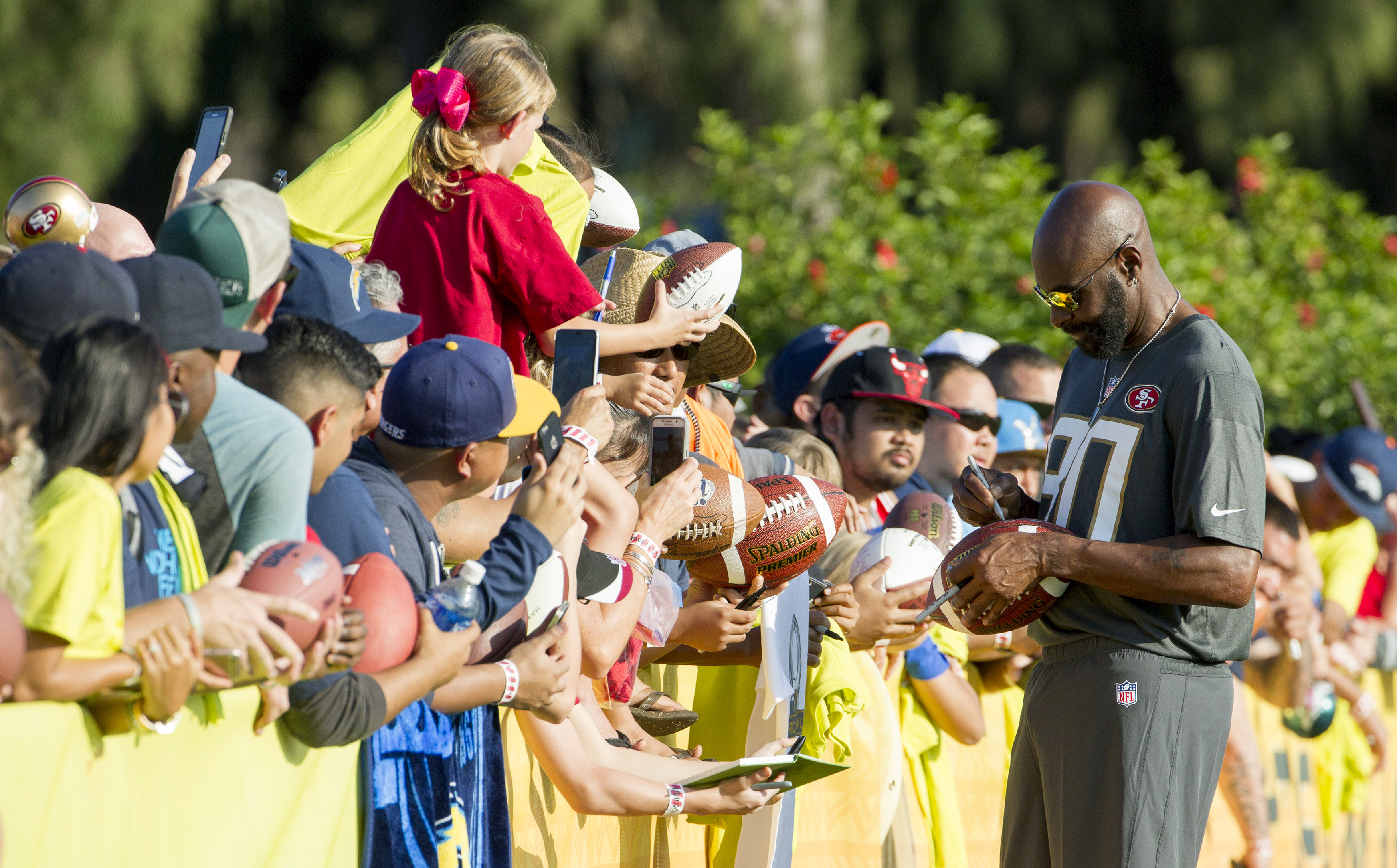 Jerry Rice, Pro Bowl legend team captain and Pro Football Hall of Famer, signs autographs for the fans during an NFL Pro Bowl football practice, Saturday, Jan. 30, 2016, in Kahuku, Hawaii. (AP Photo/Eugene Tanner)
