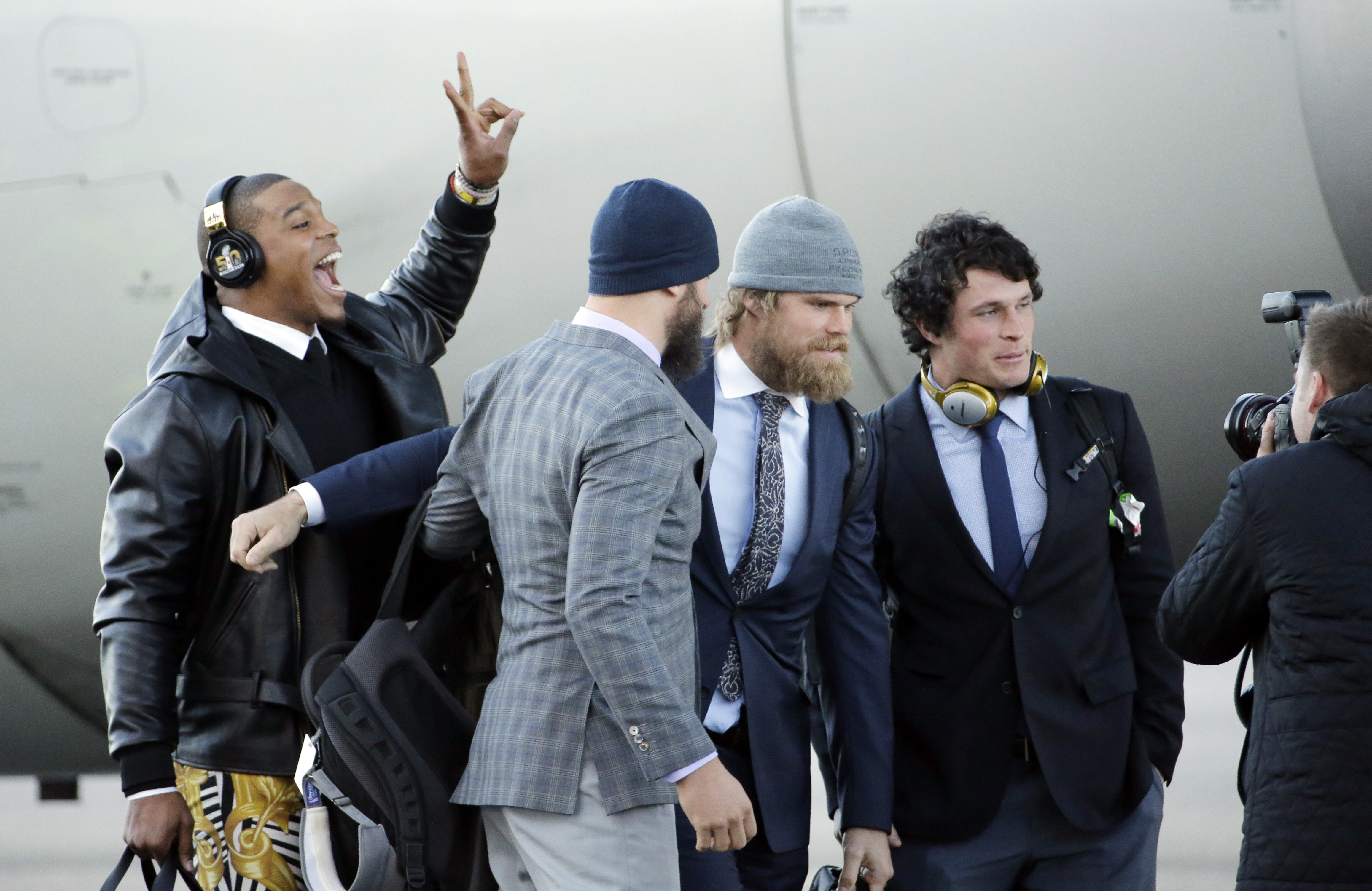 Carolina Panthers' Cam Newton jumps into a picture being taken of Luke Kuechly, right to left, Greg Olsen and Derek Anderson after getting off the plane at the Mineta San Jose International Airport as they arrive for the NFL Super Bowl football game Sunda