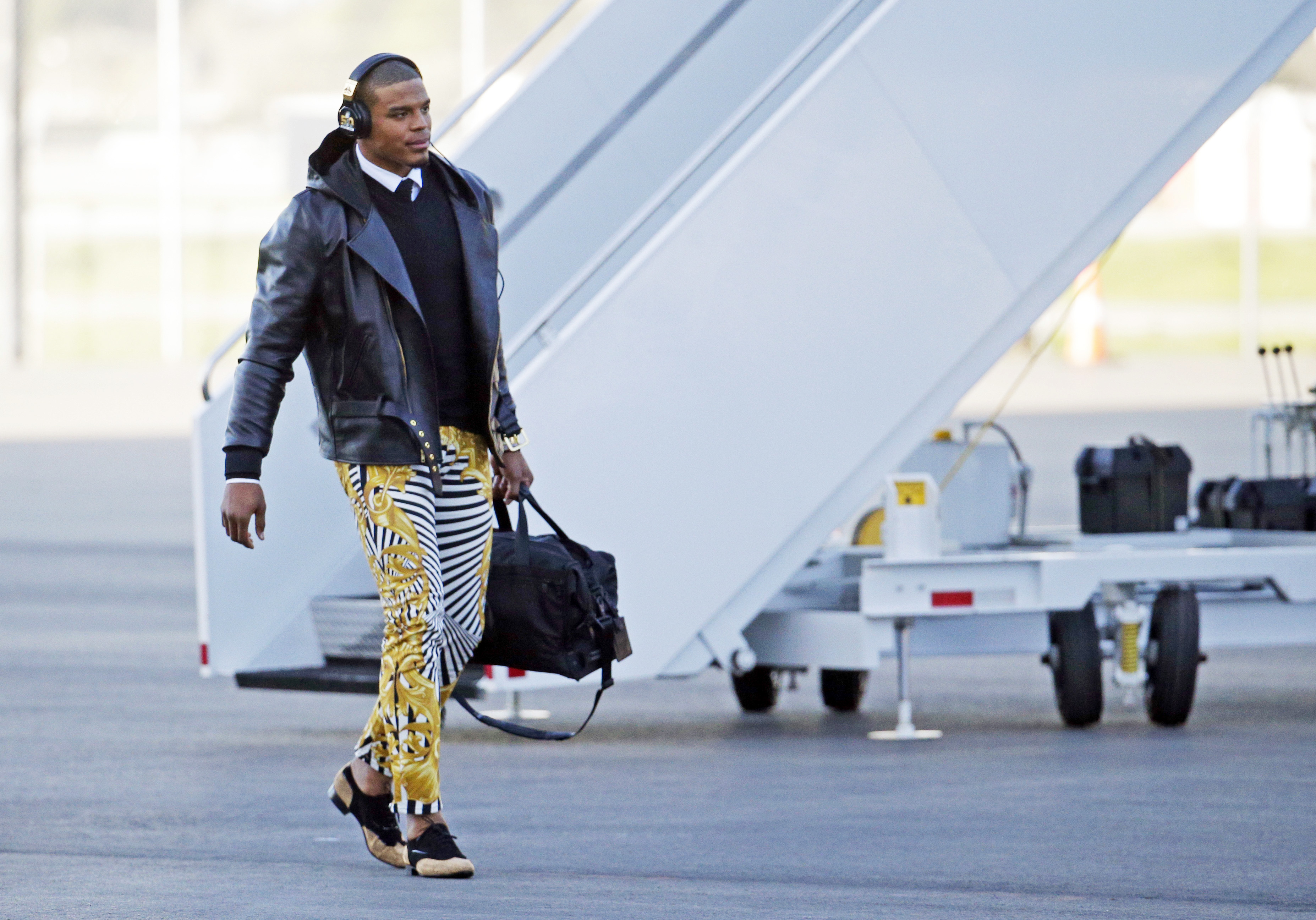 FILE - In this Jan. 31, 2016 file photo, Carolina Panthers quarterback Cam Newton gets off the plane at the Mineta San Jose International Airport in San Jose, Calif.  The Panthers play the Denver Broncos on Sunday, Feb. 7, 2015, in Super Bowl 50. Newton w