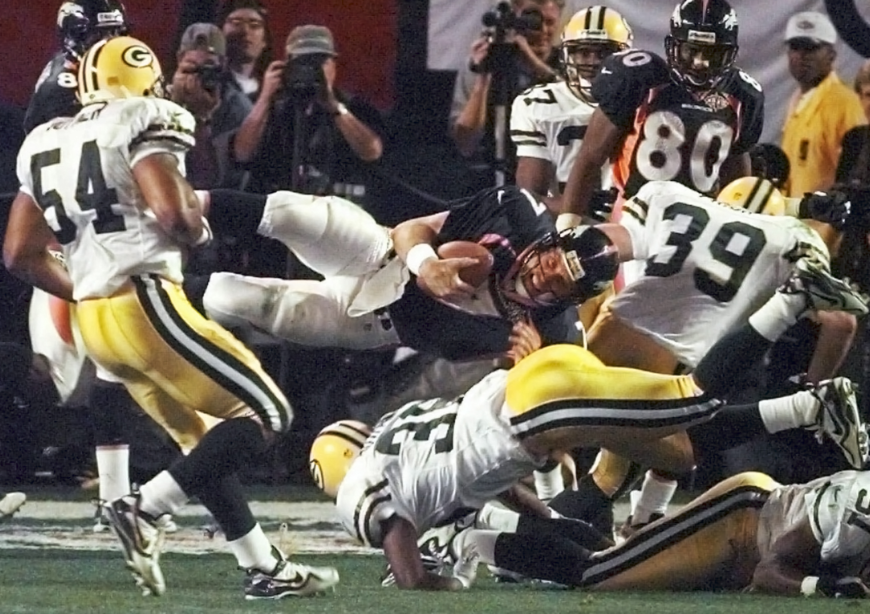 FILE - In this Jan. 25, 1998, file photo, Denver Broncos quarterback John Elway is upended Green Bay Packers' Brian Williams (51) and Elroy Butler (36) while running for a first down during the third quarter of NFL football's Super Bowl XXXII in San Diego