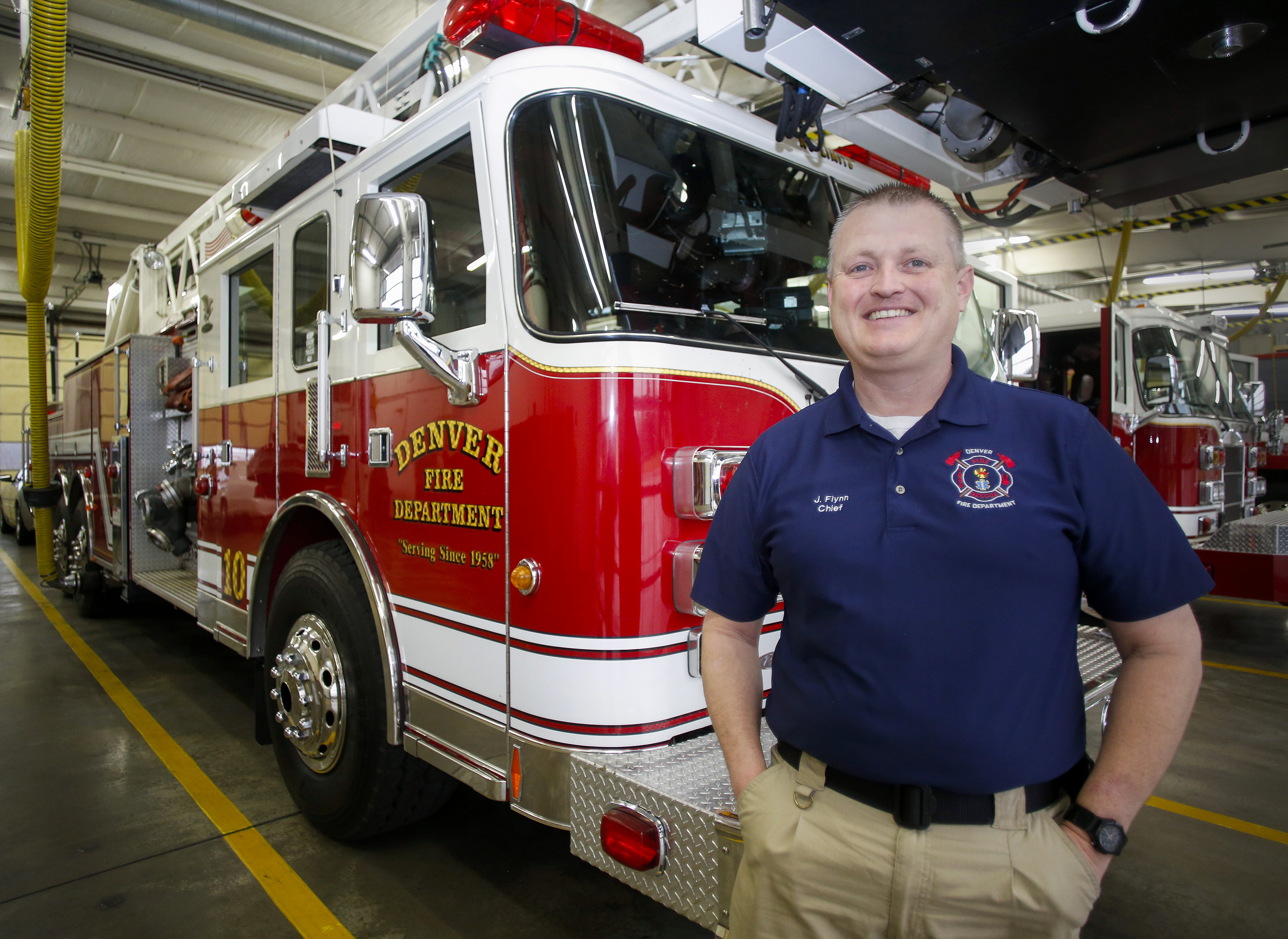 In this photo taken Wednesday, Feb. 3, 2016, Jay Flynn, fire chief of the Denver,  N.C. fire department, stands by one of his fire trucks in Denver, N.C.  Flynn is pulling for the  Carolina Panthers to defeat the Denver Broncos in the Super Bowl, as his f