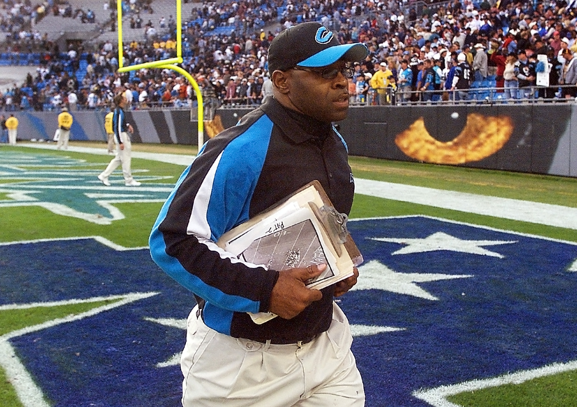FILE - In this Nov. 16, 2003, file photo, Carolina Panthers linebackers coach Sam Mills leaves the field after the Panthers' game against the Washington Redskins in Charlotte, N.C. The Panthers motto is everywhere, on stadium walls, plaques and even the t