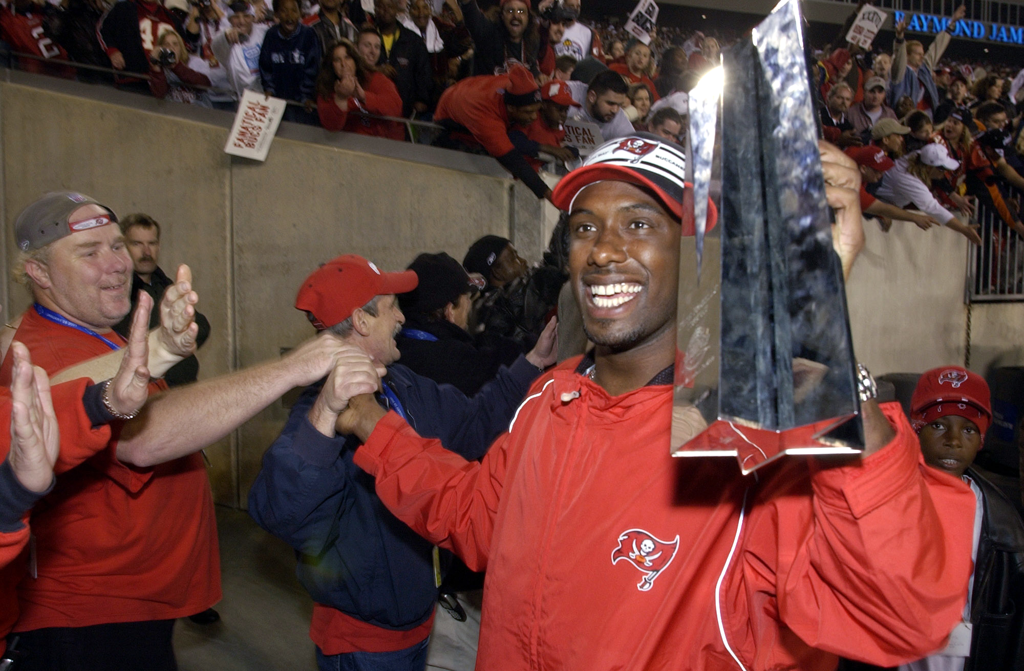 FILE - In this Jan. 27, 2003, file photo, Tampa Bay Buccaneers' Dexter Jackson holds his Super Bowl MVP trophy as he high-fives fans during a victory celebration at Raymond James Stadium in Tampa, Fla. Jackson intercepted two passes in the first half agai