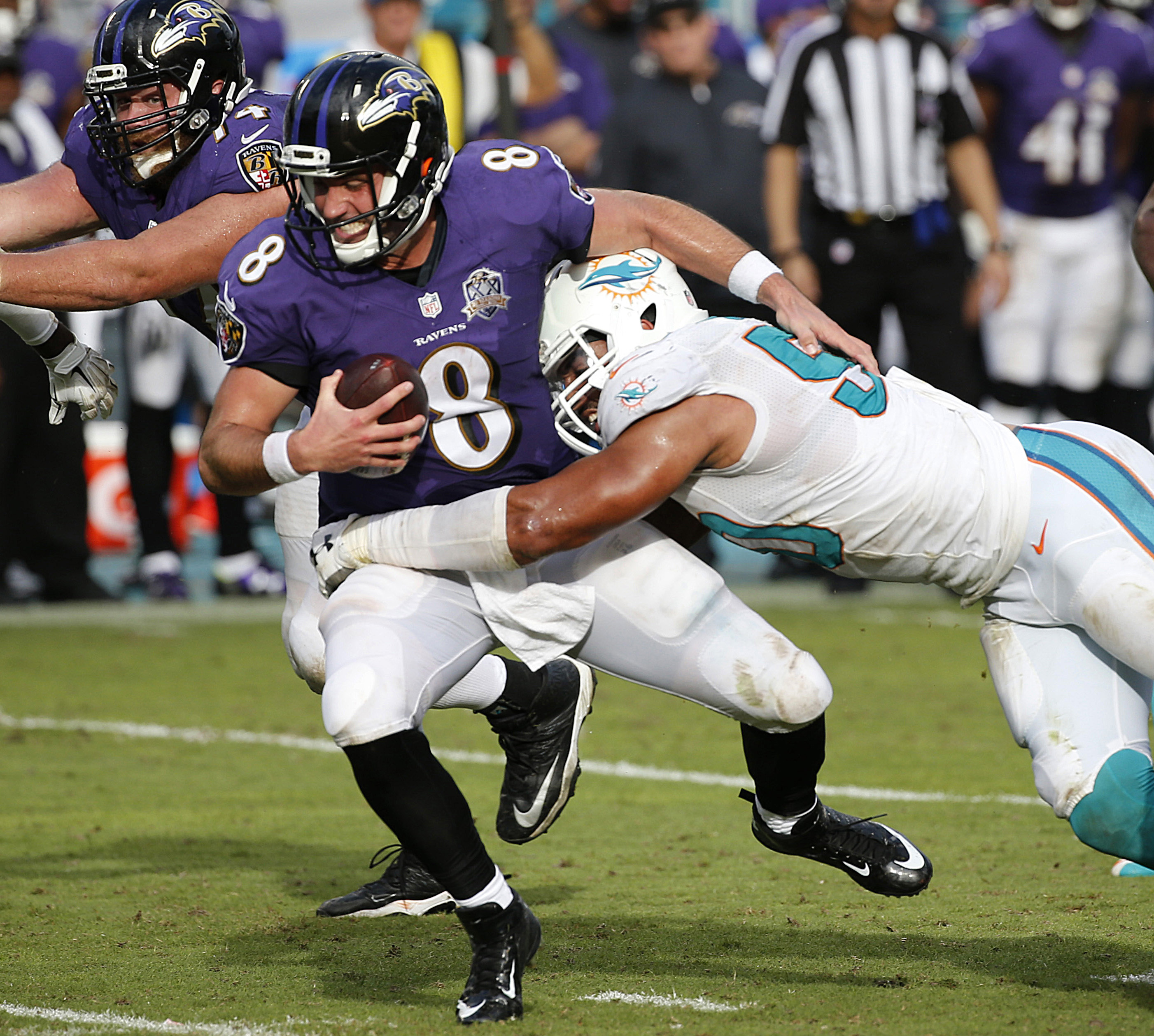 FILE - In this Dec. 6, 2015, file photo, Baltimore Ravens quarterback Matt Schaub (8) is sacked by Miami Dolphins defensive end Olivier Vernon (50), during the second half of an NFL football game, in Miami Gardens, Fla. The Miami Dolphins placed the trans