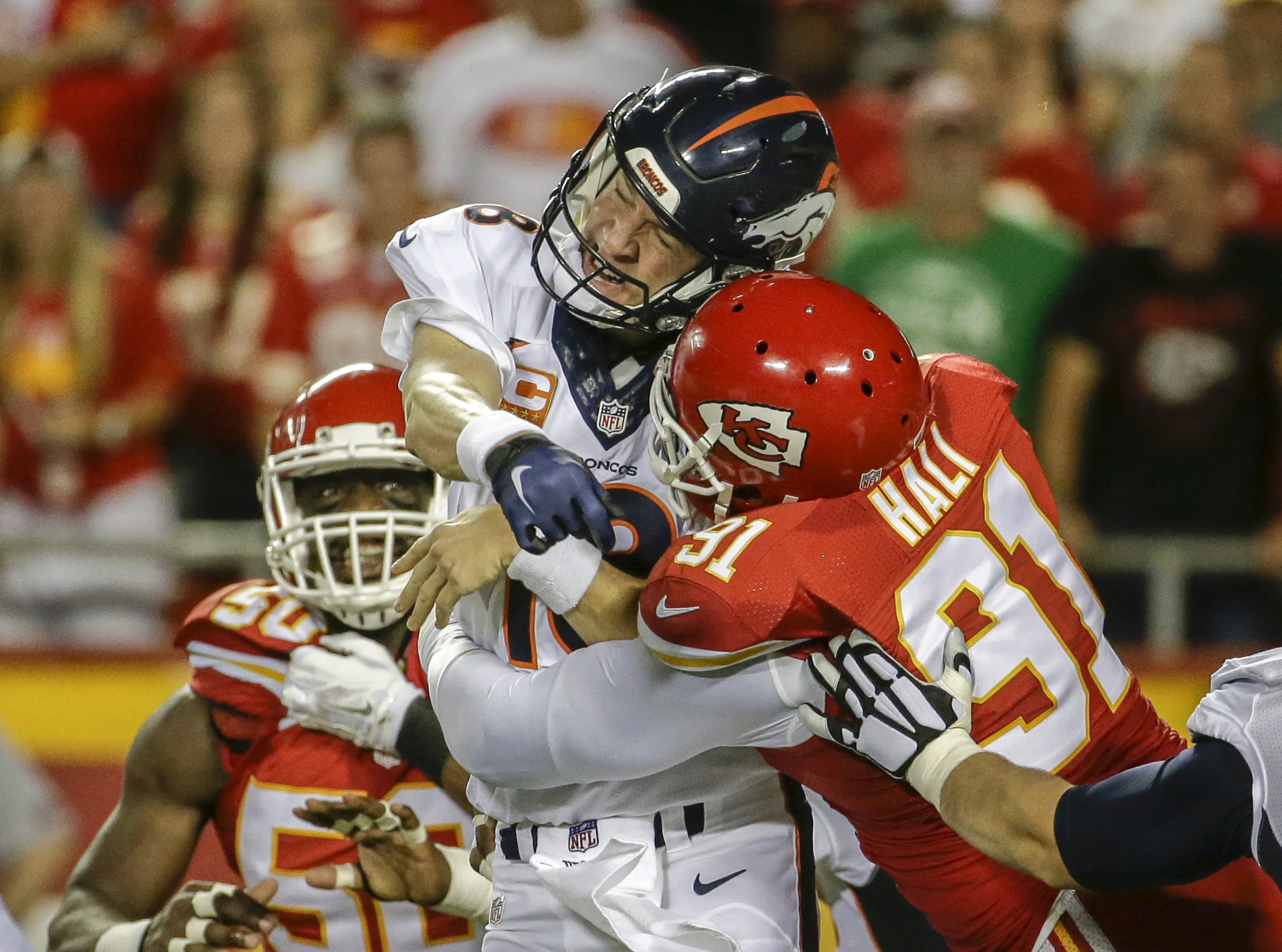 FILE - In this Sept. 17, 2015, file photo, Kansas City Chiefs linebacker Tamba Hali (91) makes contact with Denver Broncos quarterback Peyton Manning (18) after the throw, in the first half of an NFL football game in Kansas City, Mo. A person familiar wit