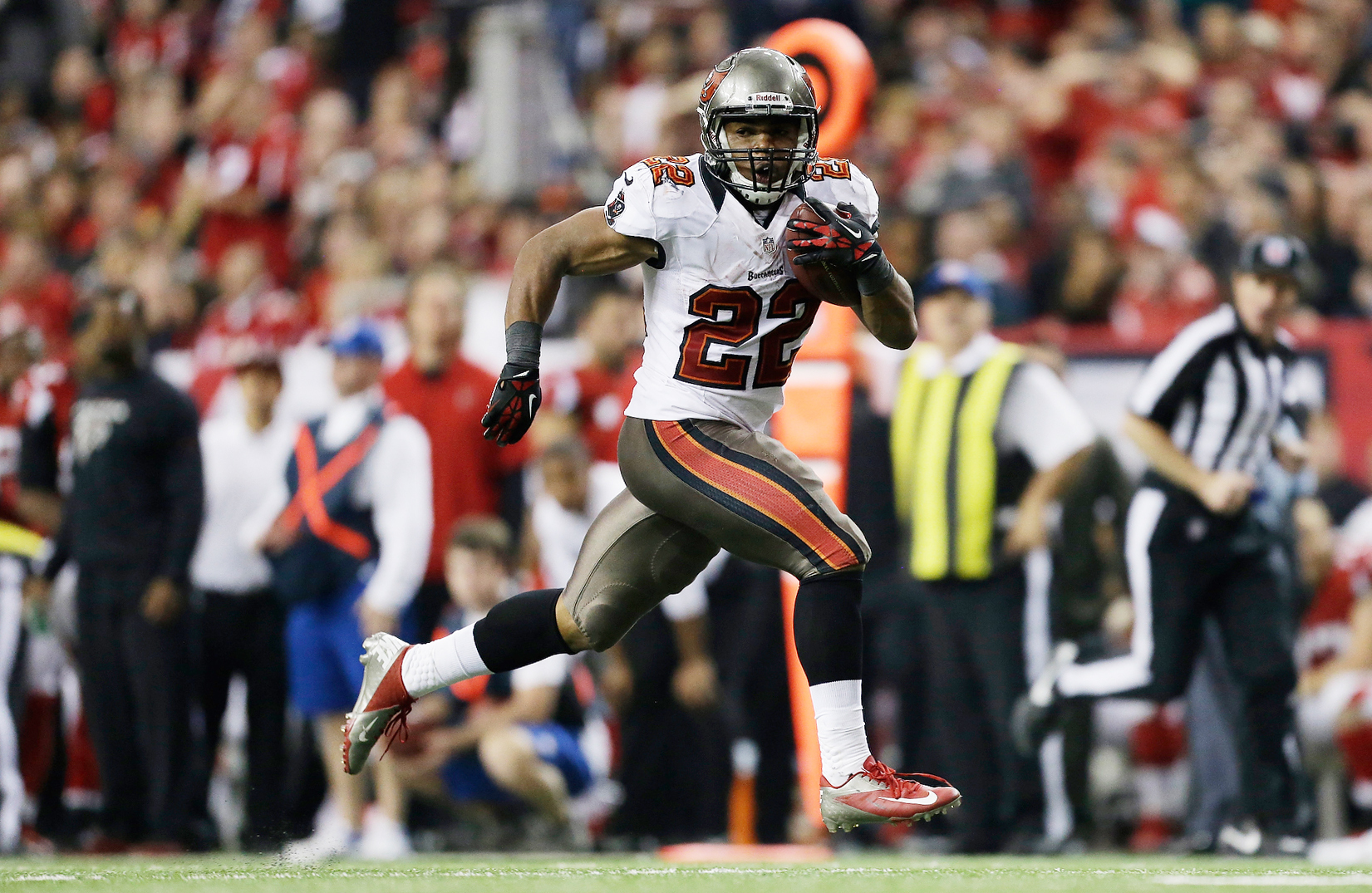 FILE - In tis Dec. 30, 2012, file photo, Tampa Bay Buccaneers running back Doug Martin (22) runs the ball alone on his way for a touchdown during the second half of an NFL football game against the Atlanta Falcons  in Atlanta. Martin is staying in Tampa,