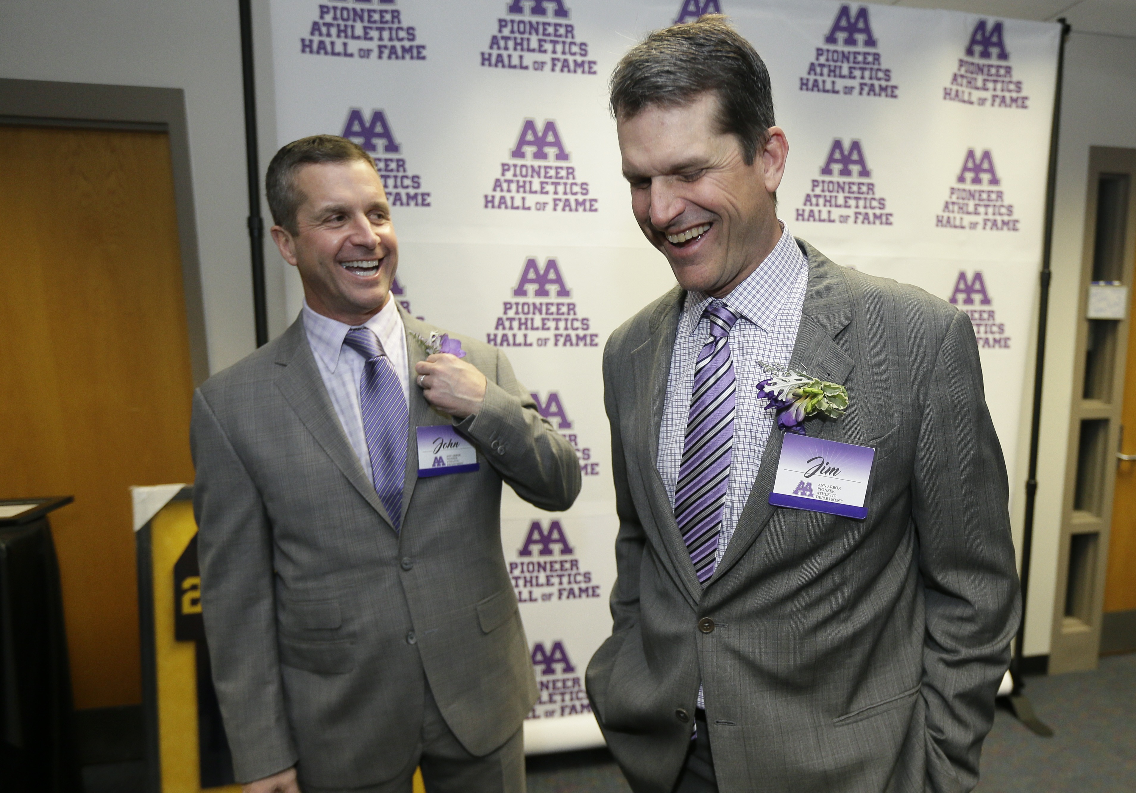 Baltimore Ravens head coach John Harbaugh, left, laughs with brother, Michigan head football coach Jim Harbaugh before their induction into the Ann Arbor Pioneer High School Hall of Fame, Friday, March 11, 2016, in Ann Arbor, Mich. (AP Photo/Carlos Osorio