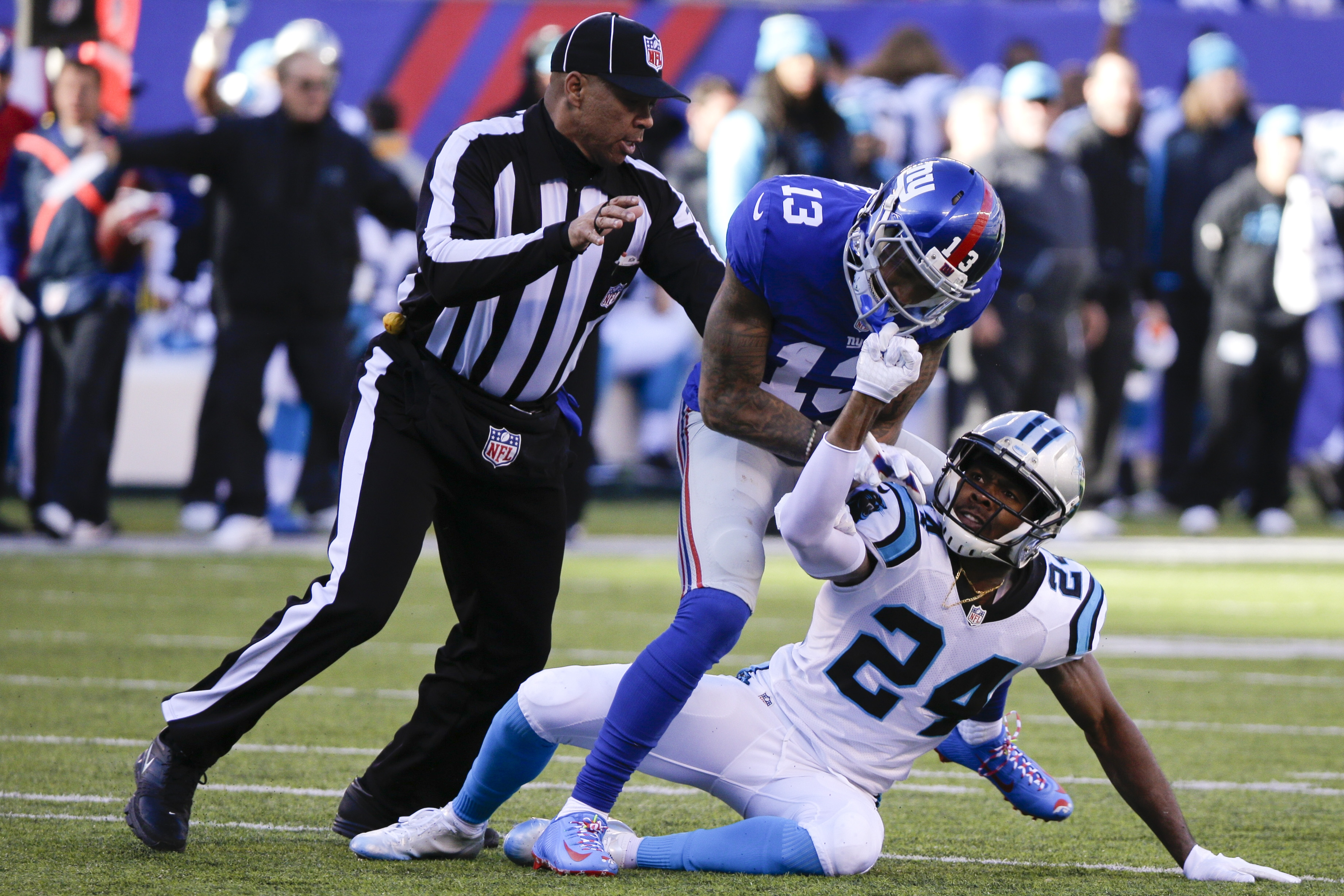 FILE - In this Dec. 20, 2015, file photo, a referee, left, separates New York Giants wide receiver Odell Beckham (13) and Carolina Panthers' Josh Norman (24) during the first half of an NFL football game Sunday, Dec. 20, 2015, in East Rutherford, N.J. The
