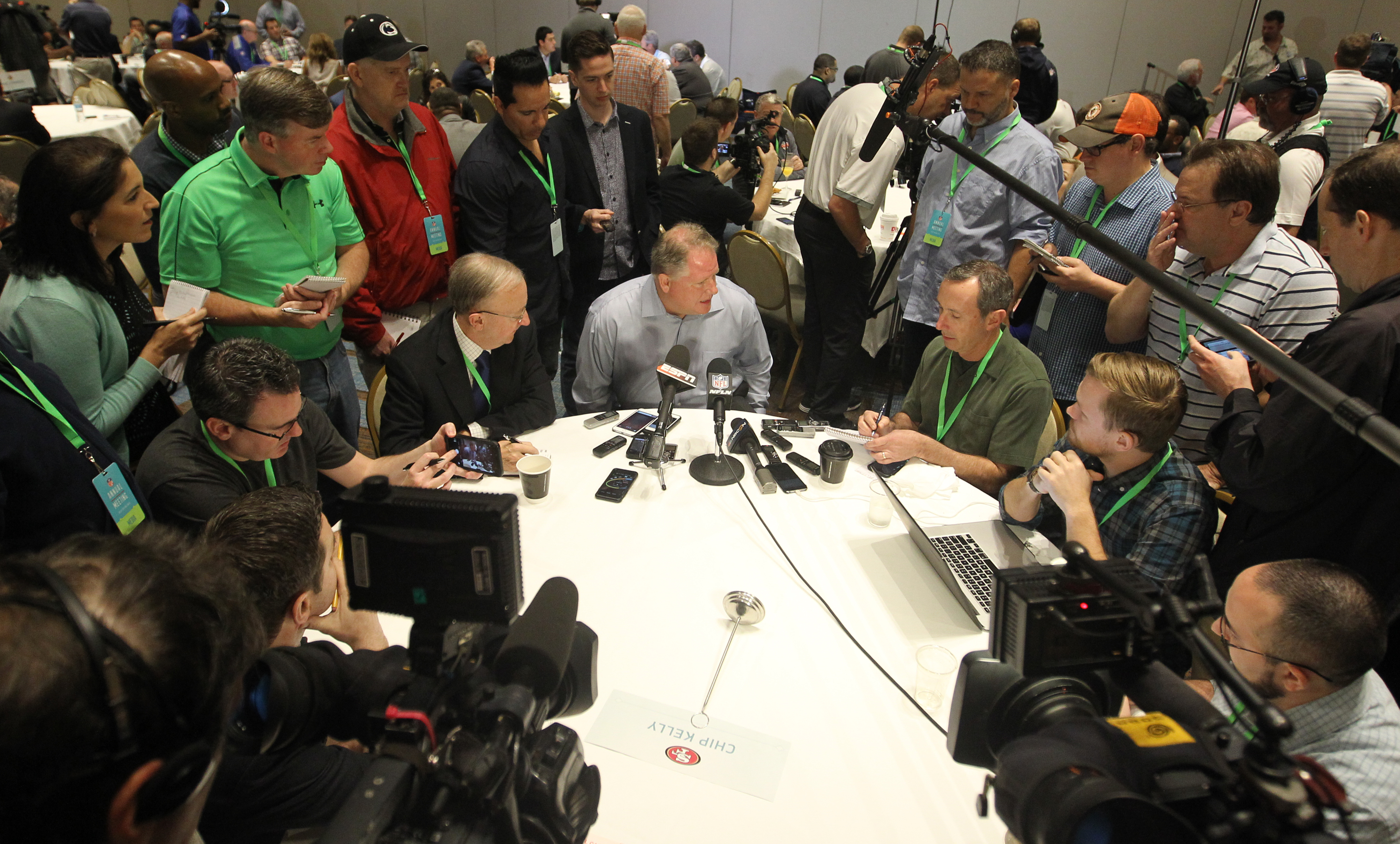 San Francisco 49ers head coach Chip Kelly, center, talks to a member of the media at the NFL owners meeting in Boca Raton, Fla., Wednesday, March 23, 2016. (AP Photo/Luis M. Alvarez)