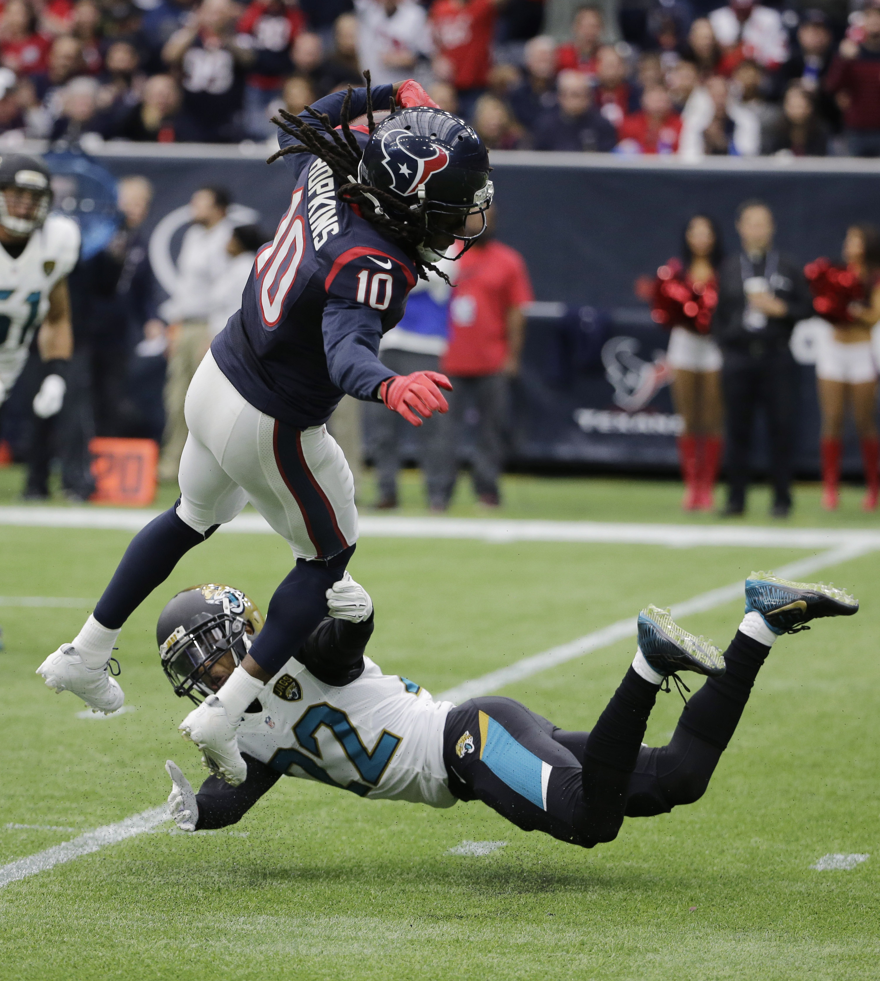 Houston Texans wide receiver DeAndre Hopkins (10) is tripped up by Jacksonville Jaguars cornerback Aaron Colvin (22) after a reception during the first half an NFL football game Sunday, Jan. 3, 2016, in Houston. (AP Photo/David J. Phillip)