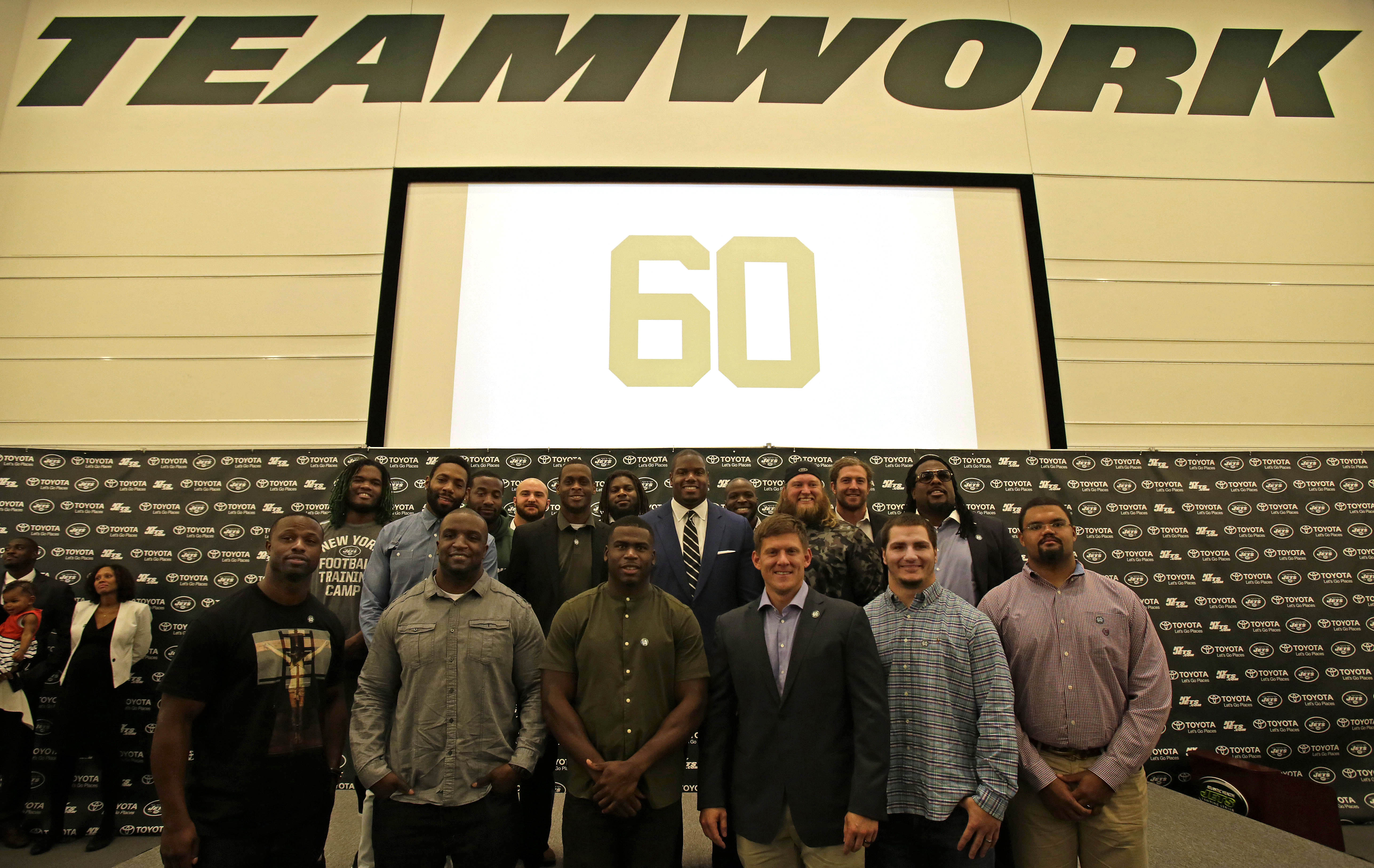 New York Jets' D'Brickashaw Ferguson (center blue suit) poses for a photo with former teammates after a press conference about retiring on Thursday, April 14, 2016 at the team's practice facility in Florham Park, N.J. (AP Photo/Adam Hunger)