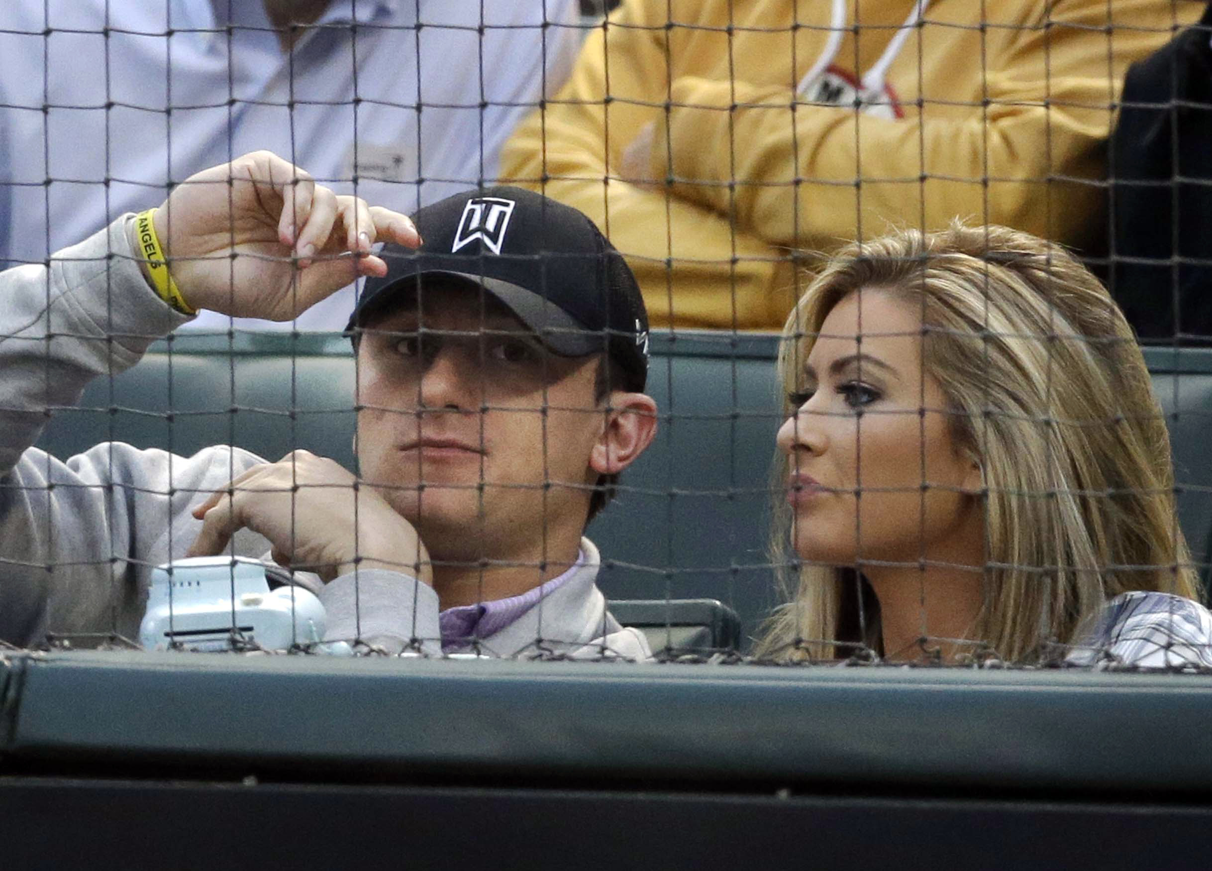 FILE - In this April 14, 2015, file photo, Cleveland Browns quarterback Johnny Manziel, left, sits with Colleen Crowley during a baseball game between the Los Angeles Angels and the Texas Rangers in Arlington, Texas. Johnny Manziel's attorney says prosecu
