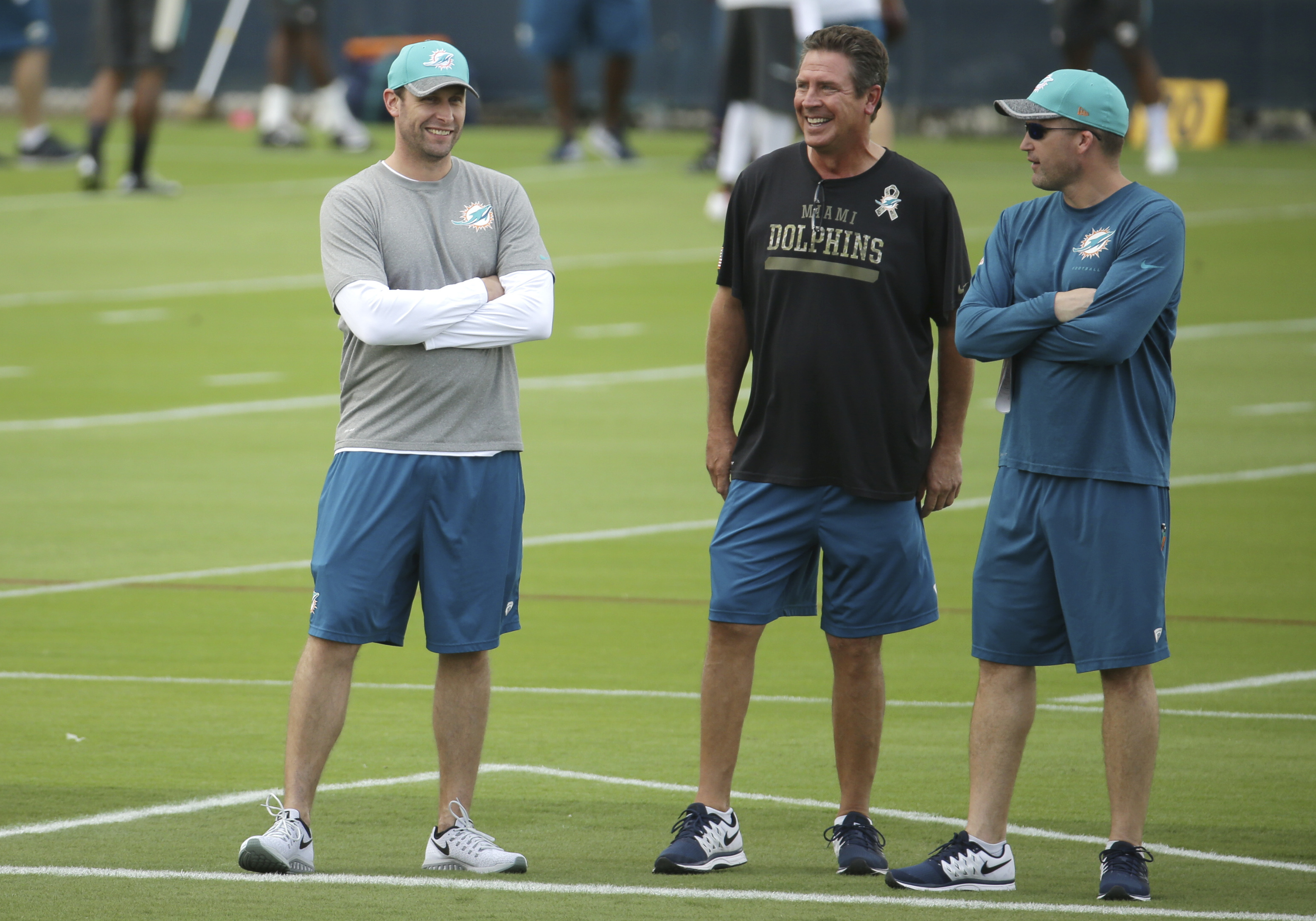 Miami Dolphins head coach Adam Gase, left, talks with former Dolphins quarterback Dan Marino, center, and assistant head coach Darren Rizzi, right, during Miami Dolphins football voluntary veterans minicamp, Tuesday, April 26, 2016, in Davie, Fla. (AP Pho